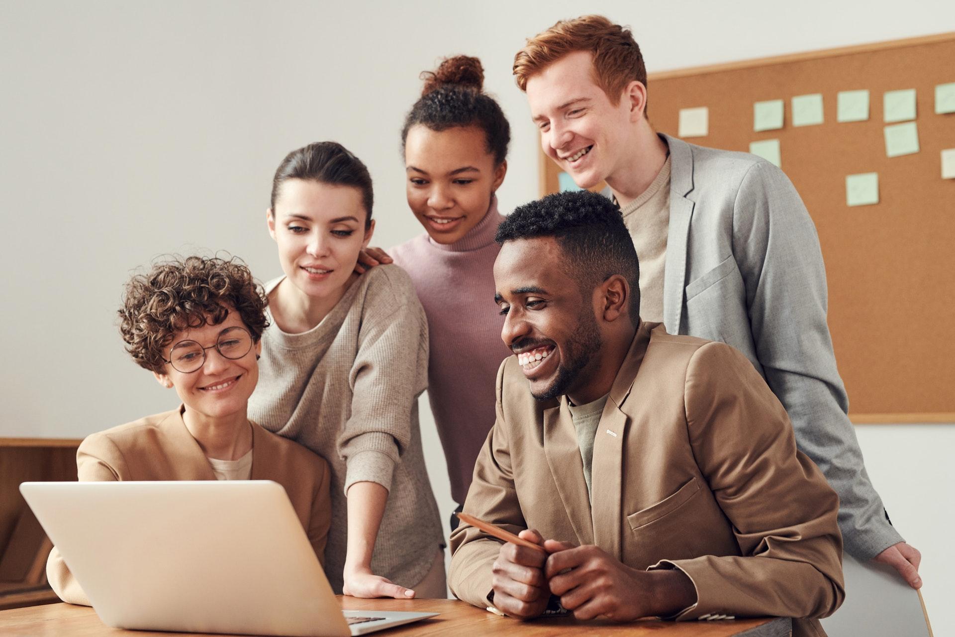 Vemos várias pessoas em uma sala de escritório olhando para um mesmo computador e sorrindo (imagem ilustrativa). Texto: empreendedorismo e intraempreendedorismo