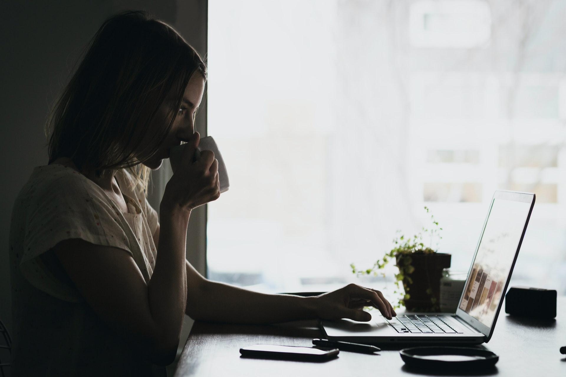 Vemos uma mulher bebendo algo de uma caneca e olhando para o computador (imagem ilustrativa). Texto: empreendedorismo e intraempreendedorismo.