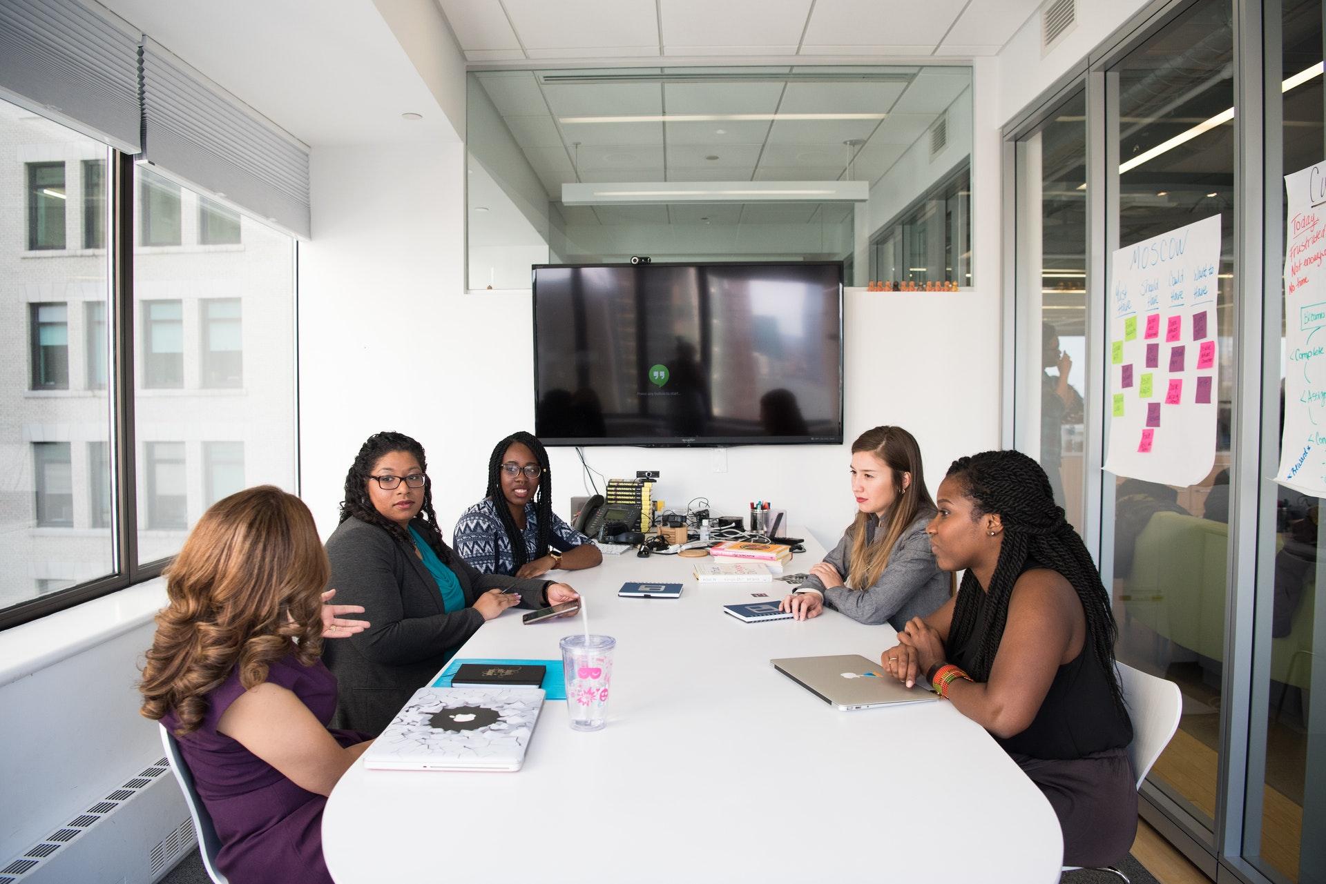 Vemos várias mulheres de negócio reunidas em uma mesa (imagem ilustrativa).