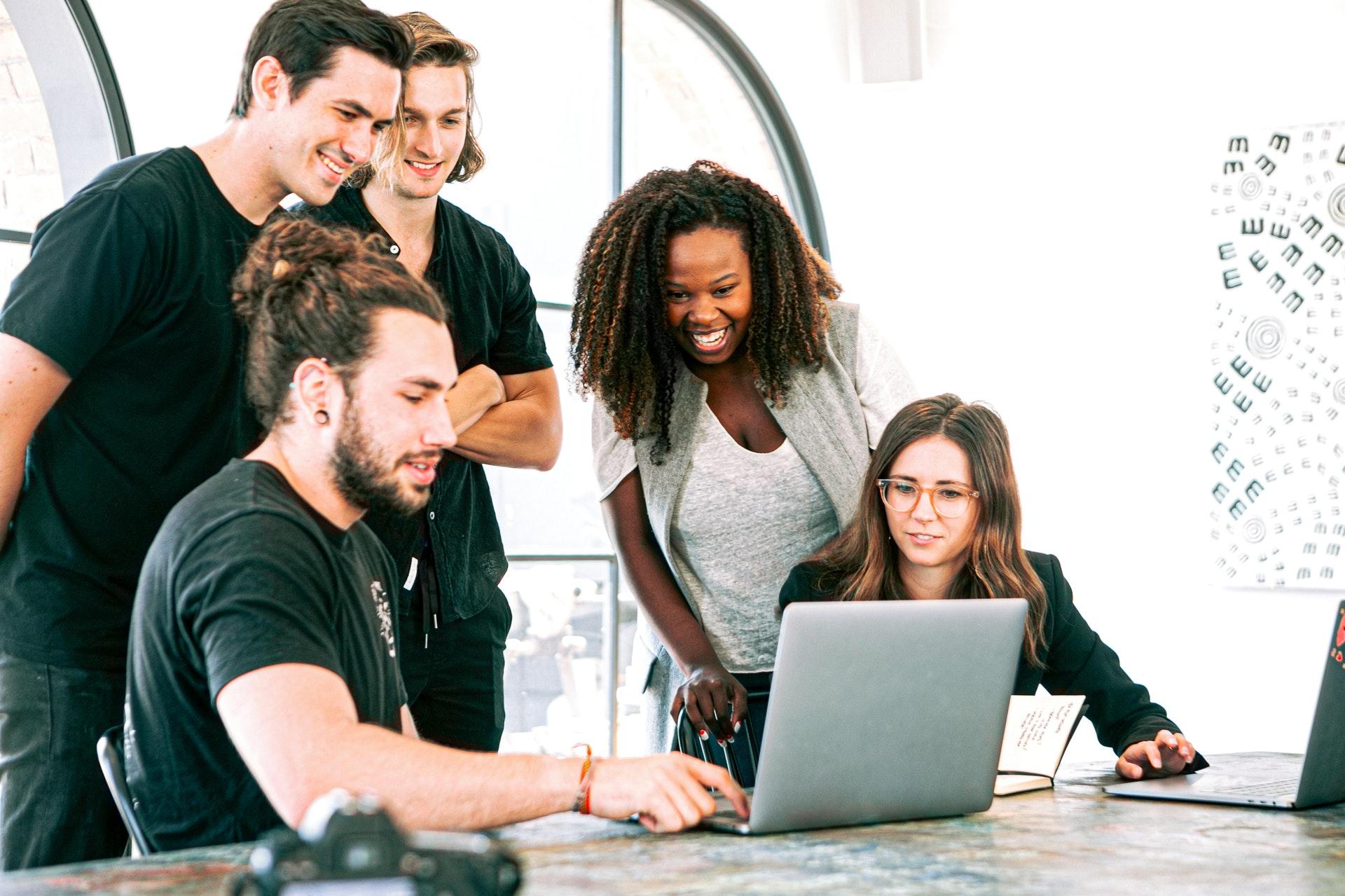 Imagem de várias pessoas olhando um computador em uma sala de escritório. imagem ilustrativa texto empreendedorismo e intraempreendedorismo.