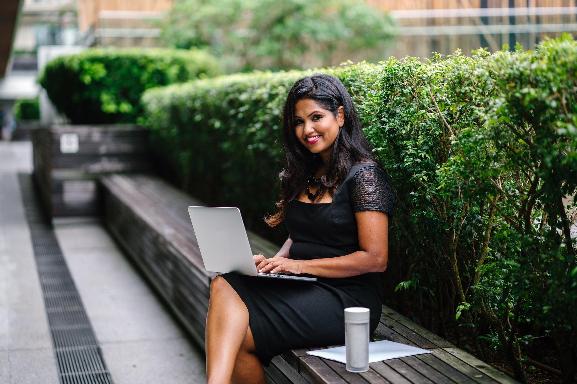 Vemos uma empresária trabalhando no que parece ser a parte externa de uma empresa (imagem ilustrativa). Texto: empreendedorismo feminino.