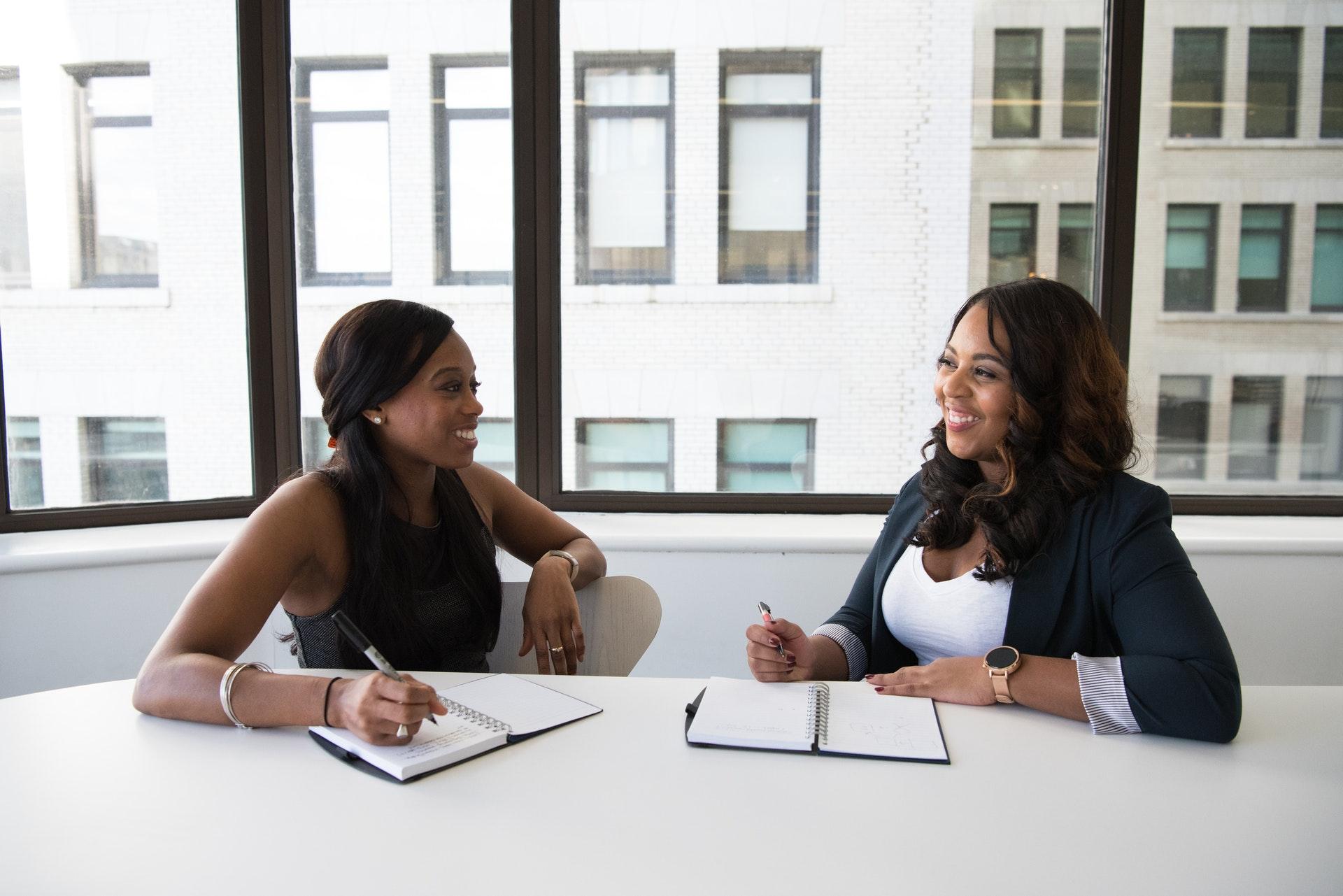 Vemos duas mulheres negras conversando em uma mesa de escritório (imagem ilustrativa).