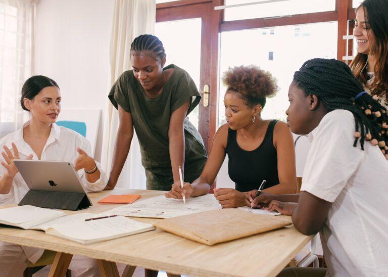 Imagem de várias mulheres em uma mesa de reunião. Imagem ilustrativa texto empreendedorismo feminino.