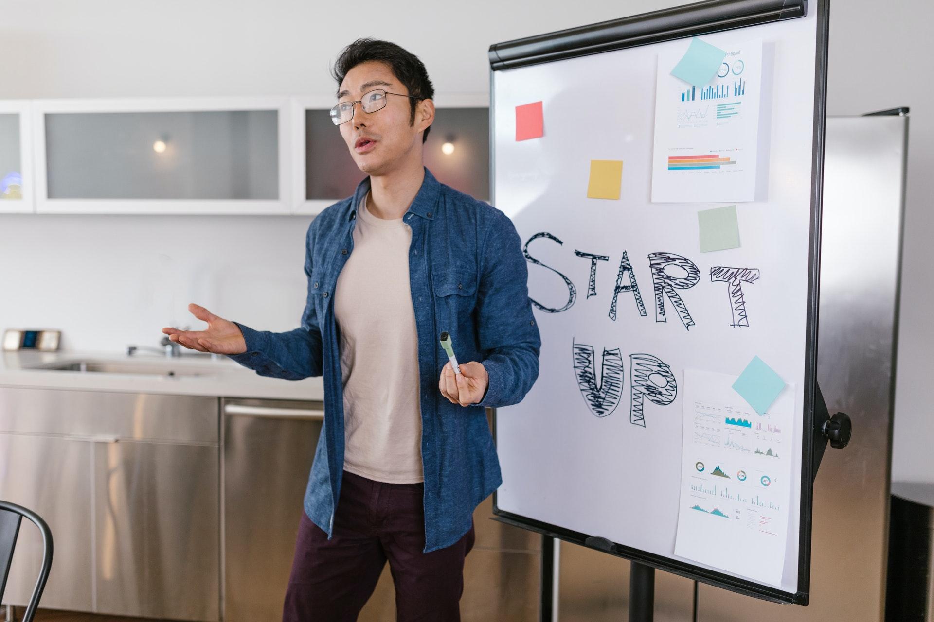 Vemos um jovem empreendedor explicando algo com o auxílio de uma lousa (imagem ilustrativa). Texto: empreendedorismo jovem.