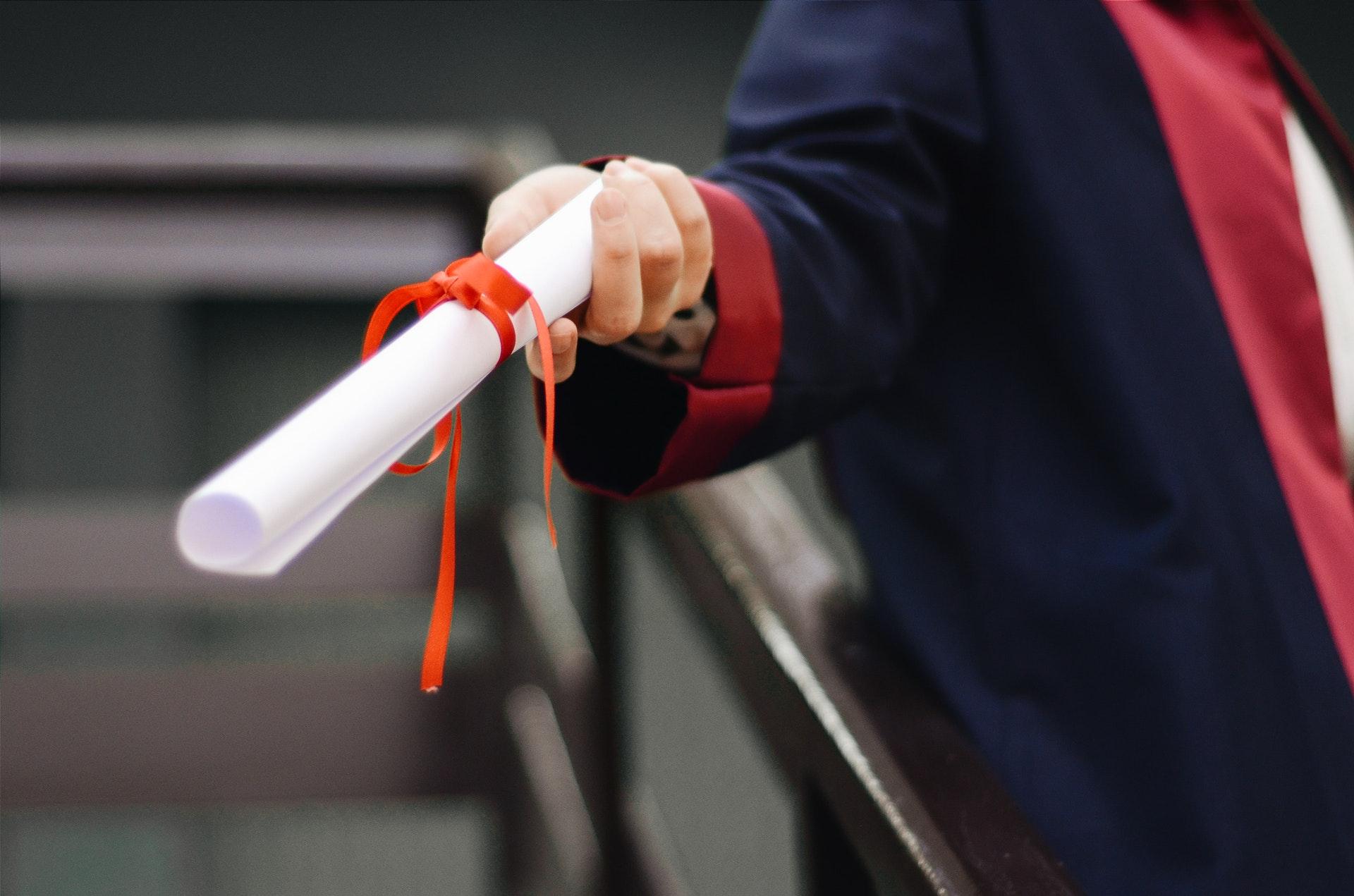 Vemos um formando segurando um diploma enrolado em formato de canudo (imagem ilustrativa). Texto: empreendedorismo jovem.