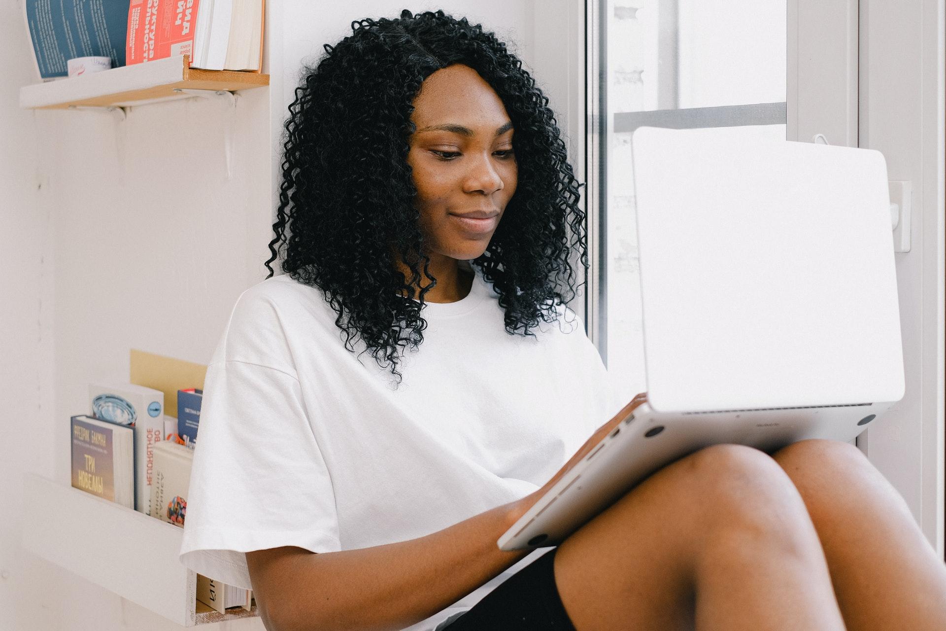 Vemos uma uma mulher sentada no sofá de casa enquanto mexe em seu computador (imagem ilustrativa). Texto: empreender em casa.