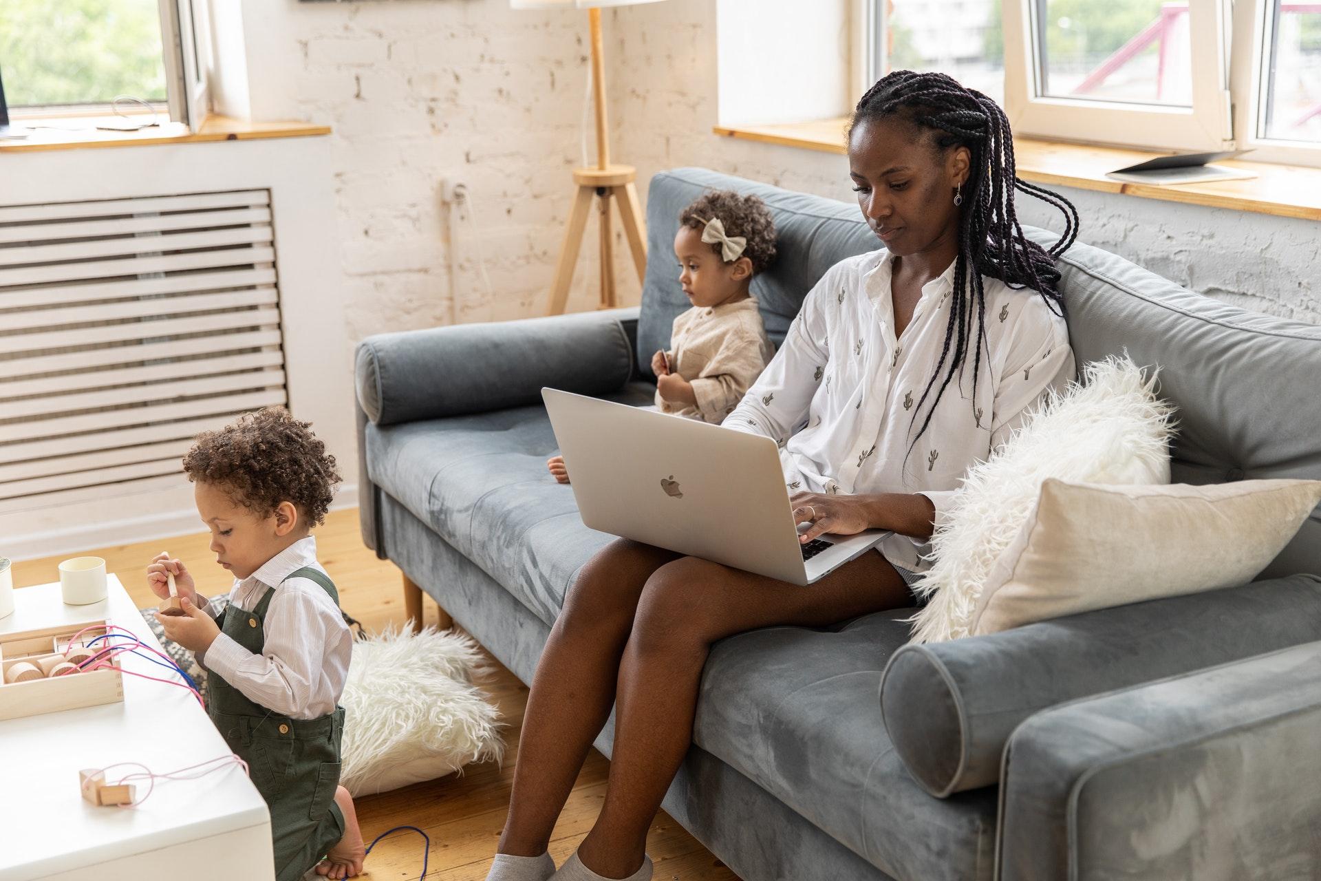 Vemos uma mulher negra, mãe de duas crianças bebês, trabalhando com seu computador no colo enquanto as crianças brincam na sala onde todos estão (imagem ilustrativa). Texto: empreender em casa.