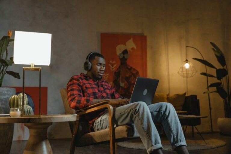 Imagem de um homem trabalhando no computador sentado no sofá de casa. Imagem ilustrativa texto empreender em casa.