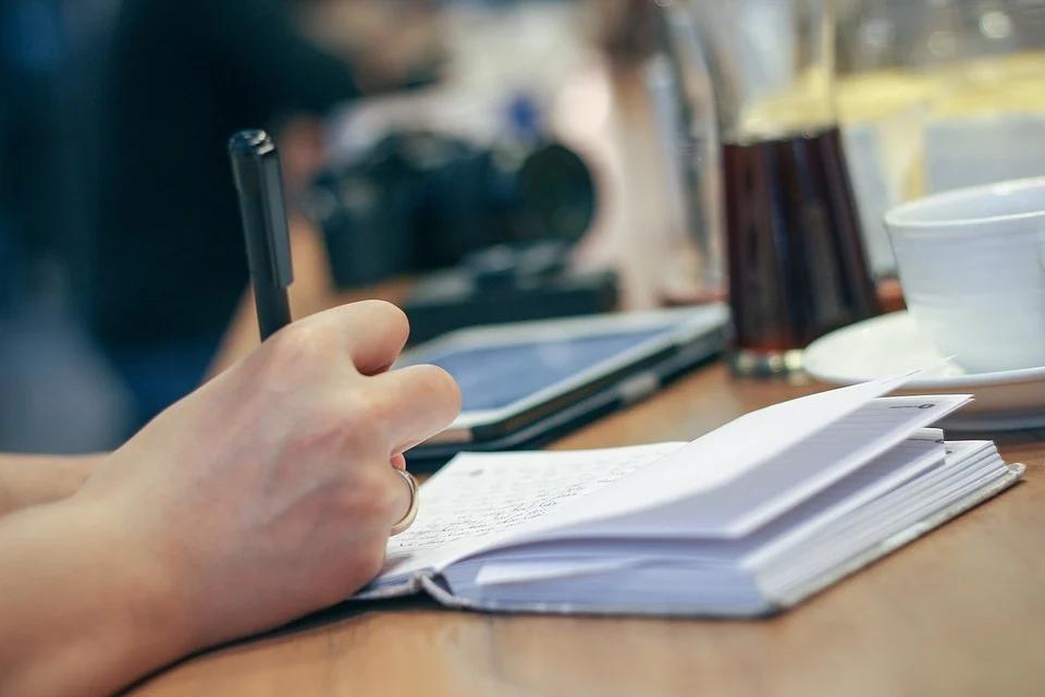 moça fazendo anotações em um caderno