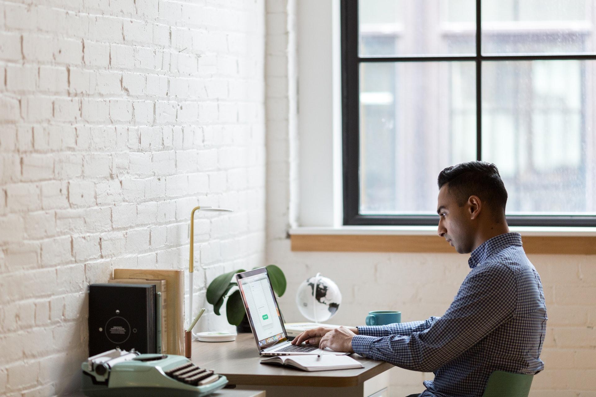 Vemos um empresário em uma mesa de escritório em sua casa (imagem ilustrativa). Texto: empresário individual.