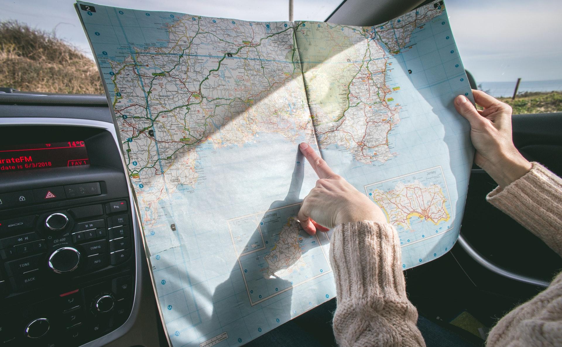 Uma pessoa, dentro de um carro, segura um mapa aberto enquanto aponta para uma região específica indicando o caminho (imagem ilustrativa). Texto: empresário individual.
