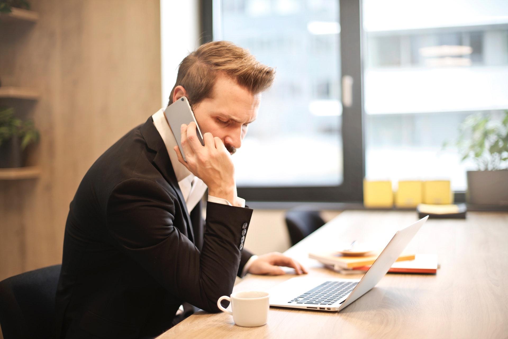 Imagem de um home falando ao telefone em uma mesa de escritório. Imagem ilustrativa texto empresário individual.