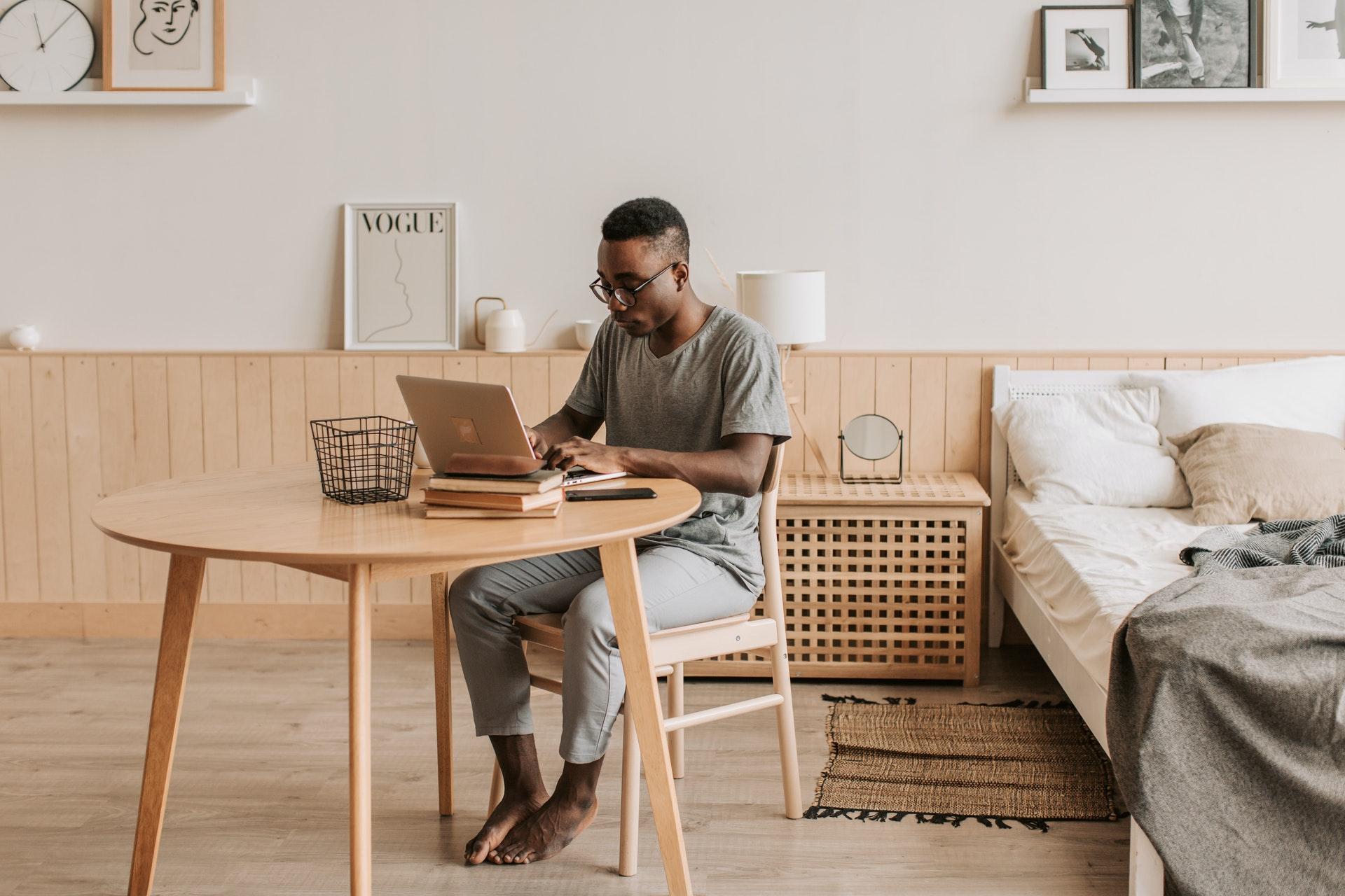 Vemos um homem negro trabalhando em seu quarto (imagem ilustrativa). Texto: franquia TZ Viagens.
