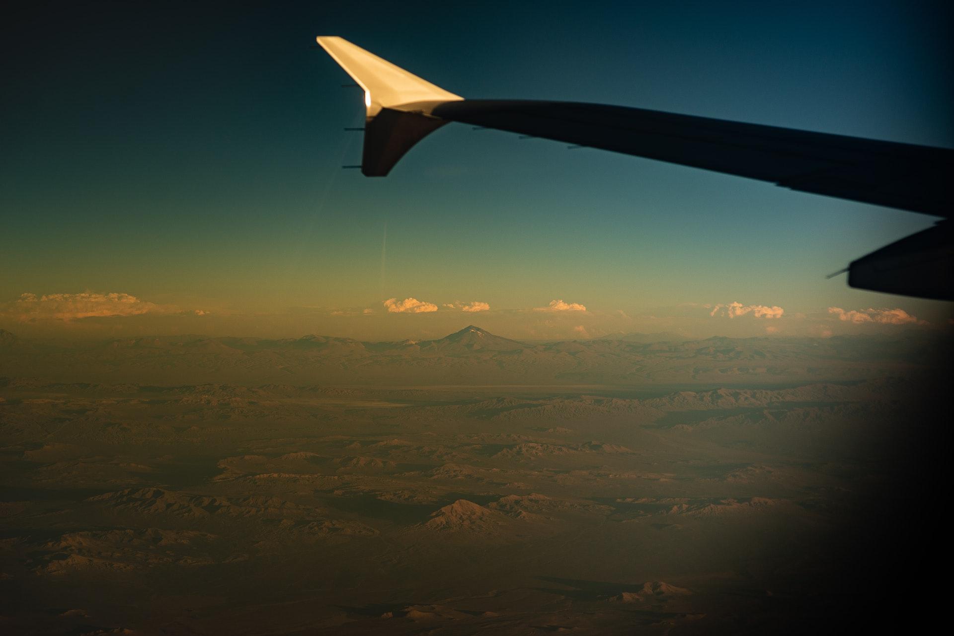 Vemos parte da asa de um avião no céu (imagem ilustrativa). Texto: franquia accorhotels.