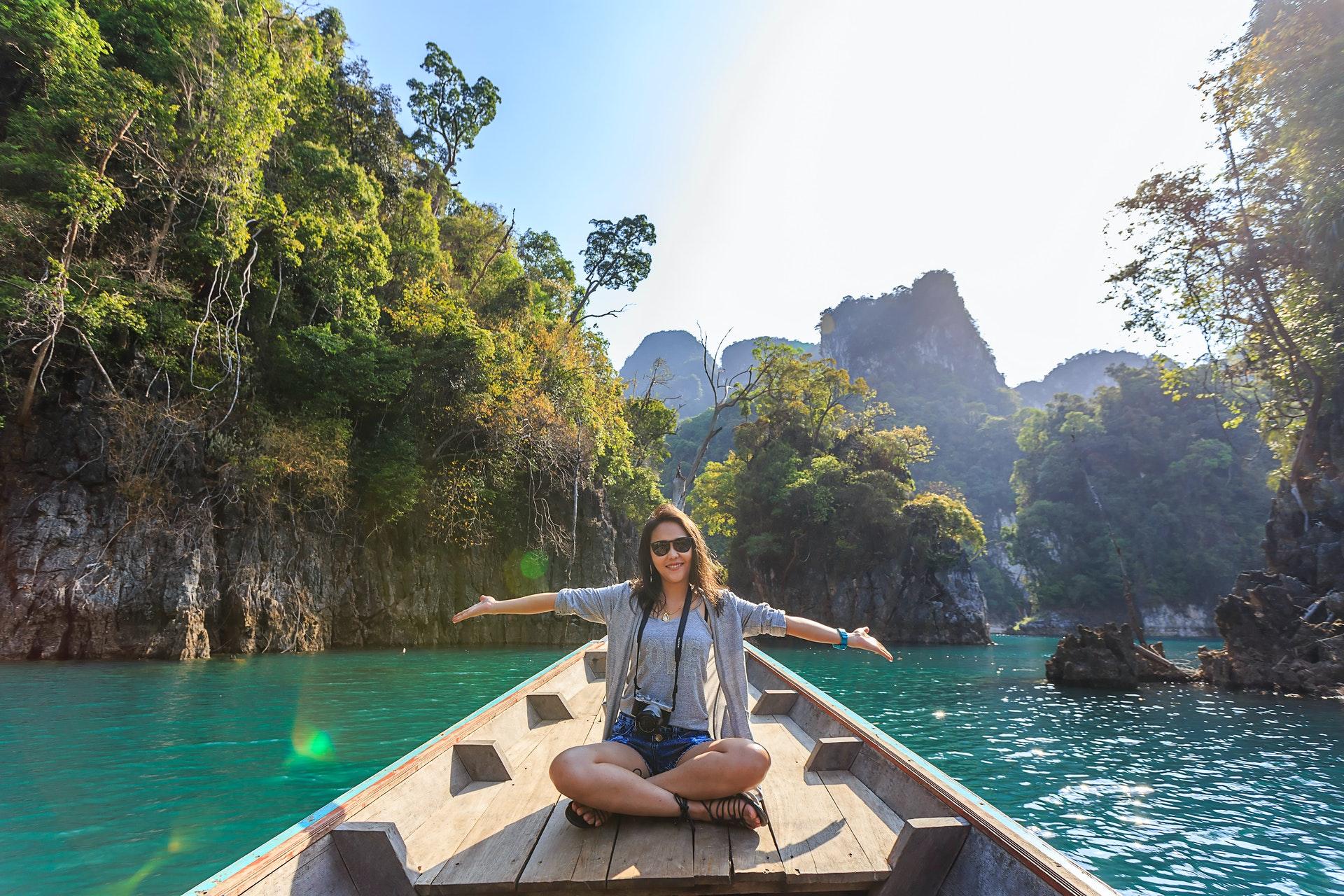Vemos uma mulher passeando por um rio em uma canoa (imagem ilustrativa). Texto: franquia CI Intercâmbio.