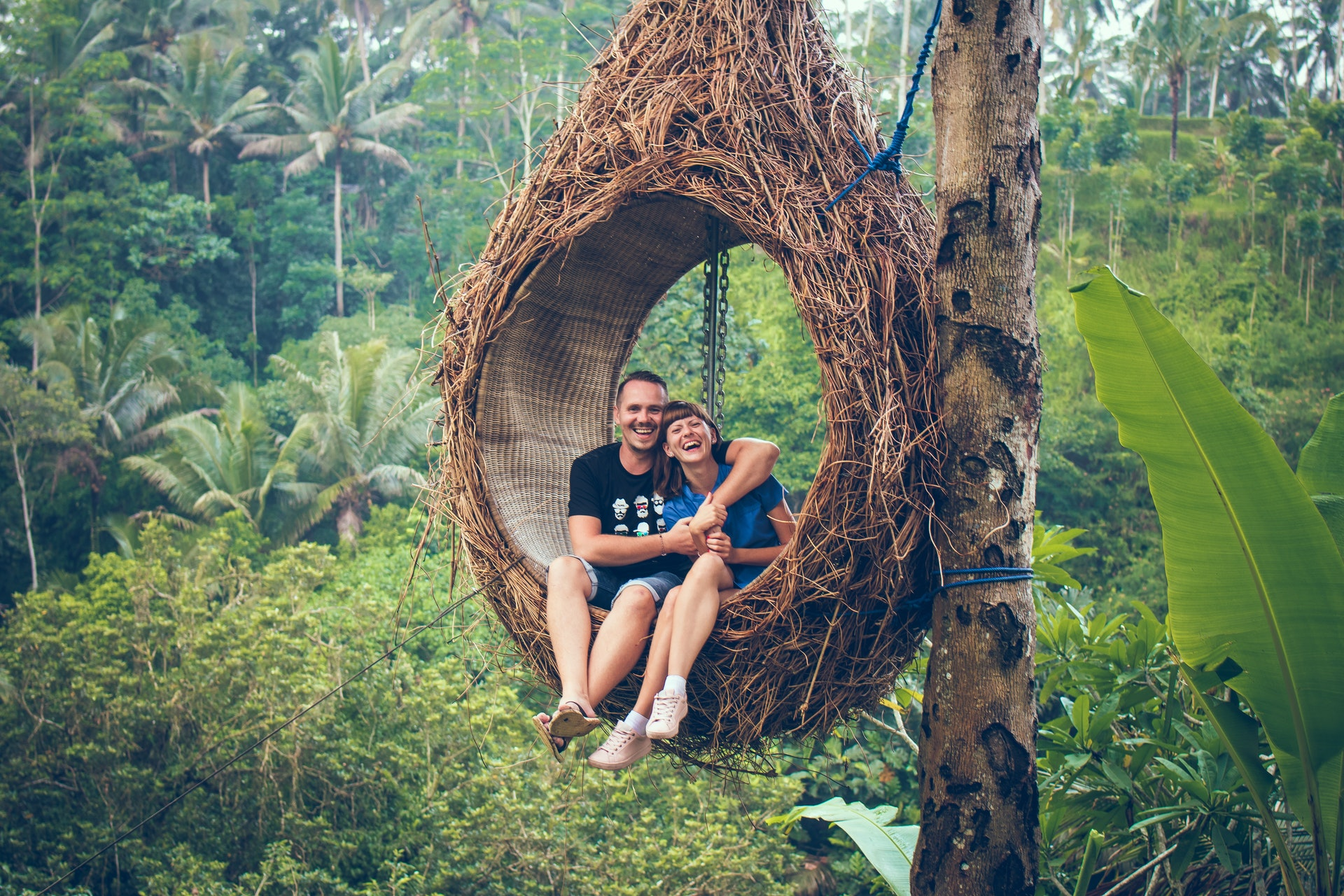 Vemos um casal (homem e mulher) em um balanço pendurado numa árvore (imagem ilustrativa). Texto: franquia CI Intercâmbio.