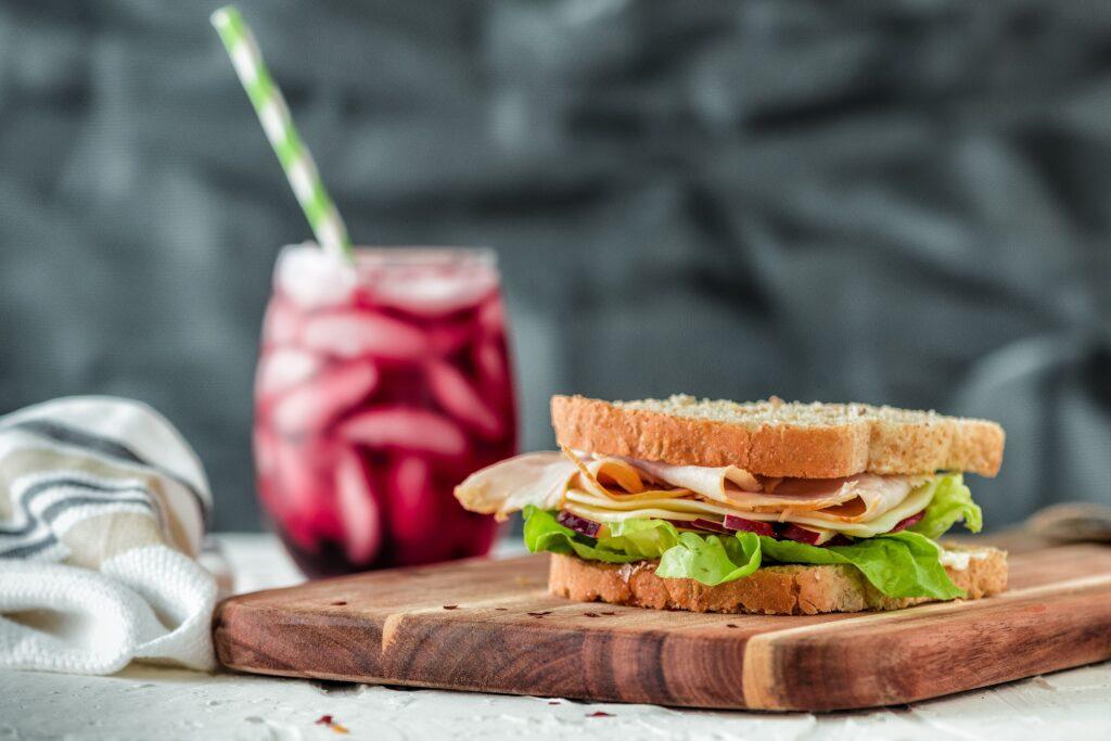 Foto de um sanduíche de pão de forma integral com recheio de alface, peito de peru e queijo em cima de uma tábua de madeira. Ao fundo vemos um copo de suco roxo com canudo imagem ilustrativa texto franquia de açaí