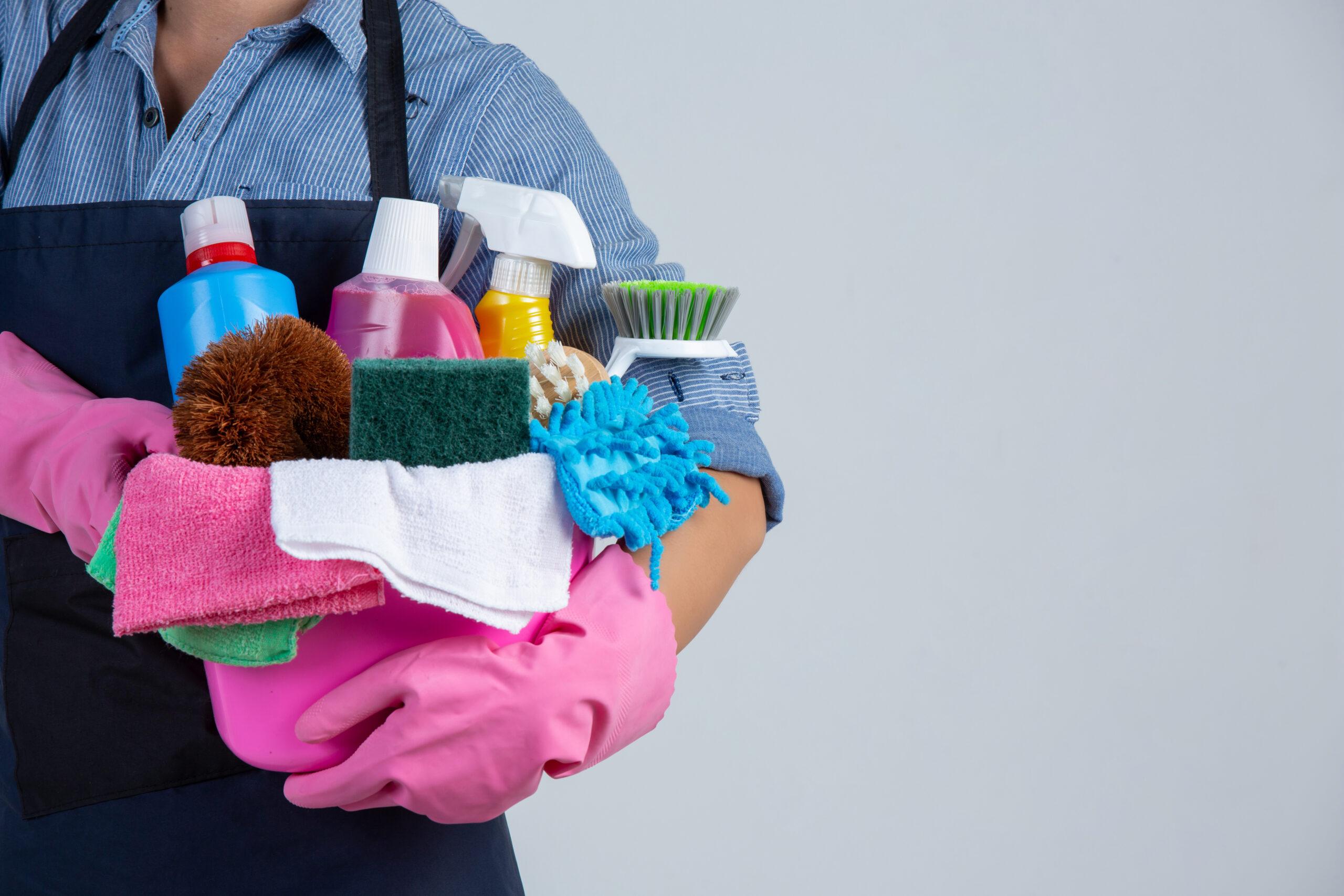 Vemos uma pessoa segurando um balde cheio de produtos de limpeza dentro (imagem ilustrativa). Texto: franquia de produtos de limpeza.