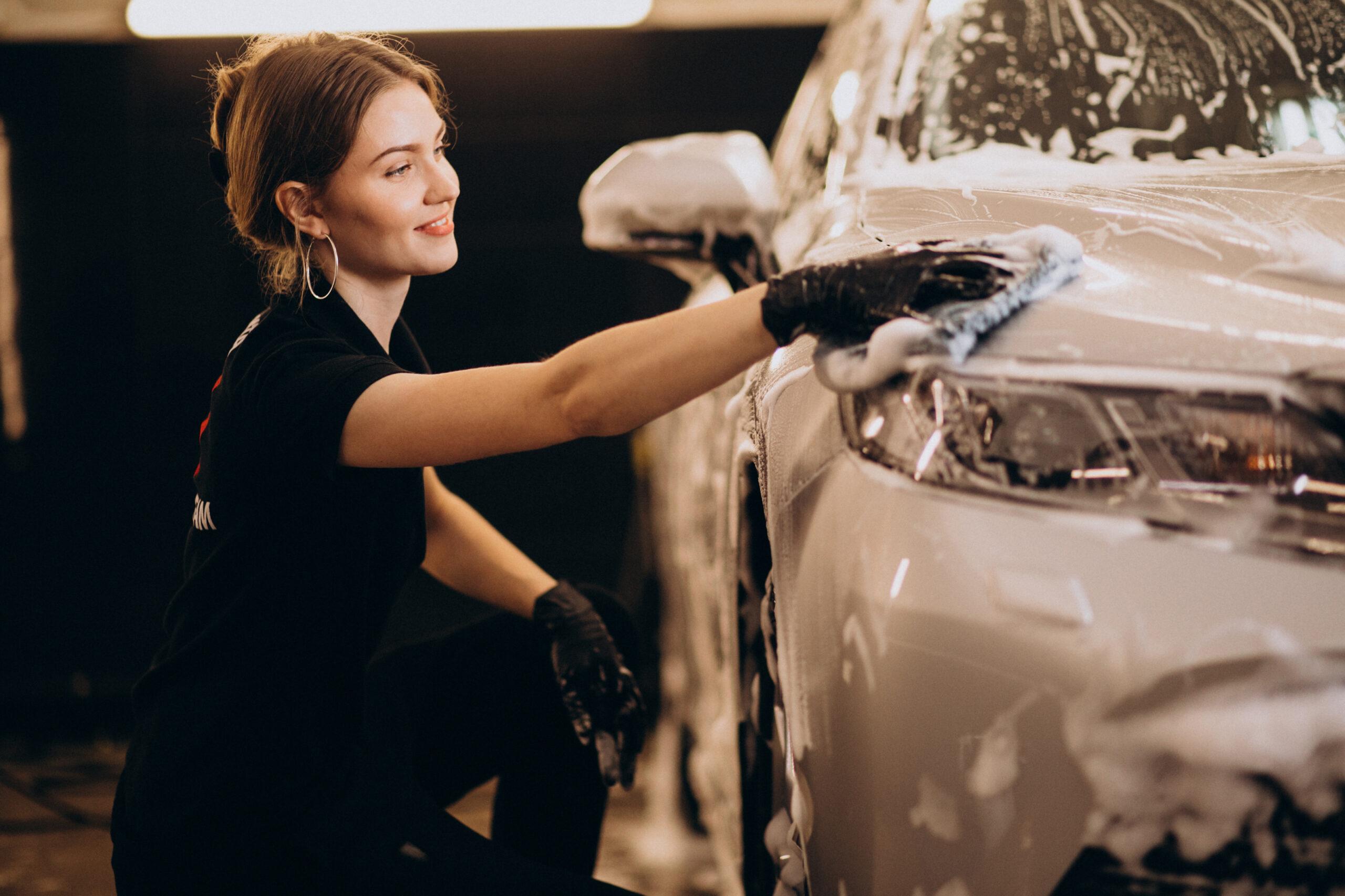 Vemos uma mulher lavando um carro (imagem ilustrativa). Texto: franquia de produtos de limpeza.