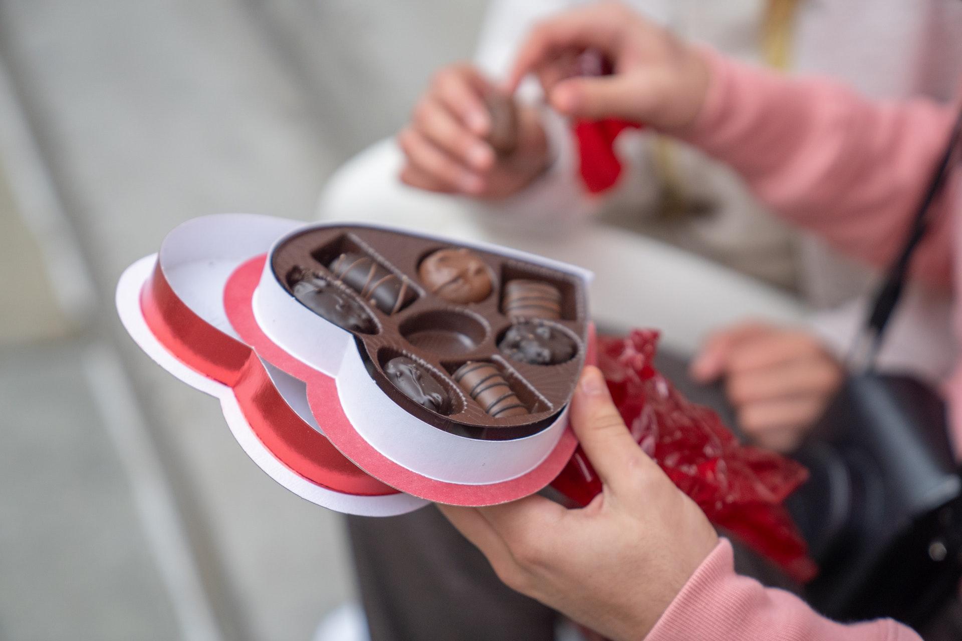 Vemos uma pessoa compartilhando uma caixa de bombons em formato de coração com a outra (imagem ilustrativa). Texto: franquia kopenhagen.