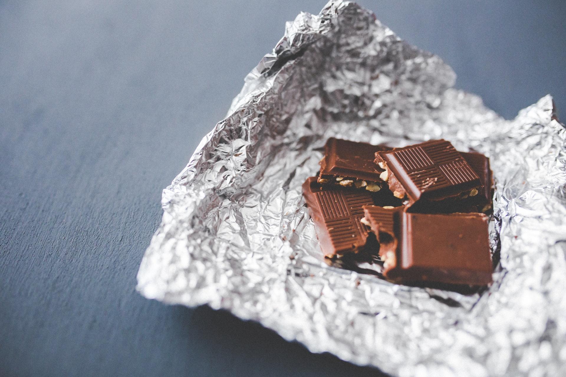 Vemos alguns pedaços de chocolate sobre papel alumínio (imagem ilustrativa). Texto: franquia Kopenhagen.