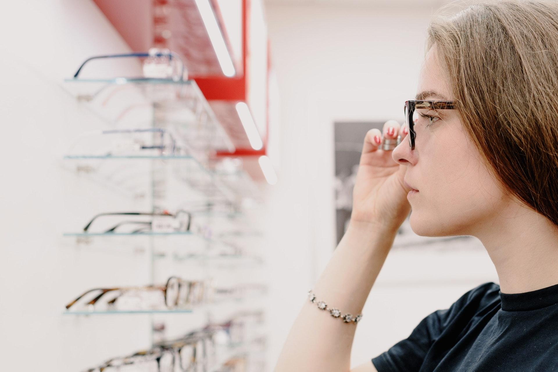 Imagem de uma mulher olhando uma prateleira cheia de óculos. Imagem ilustrativa texto franquia ótica diniz.