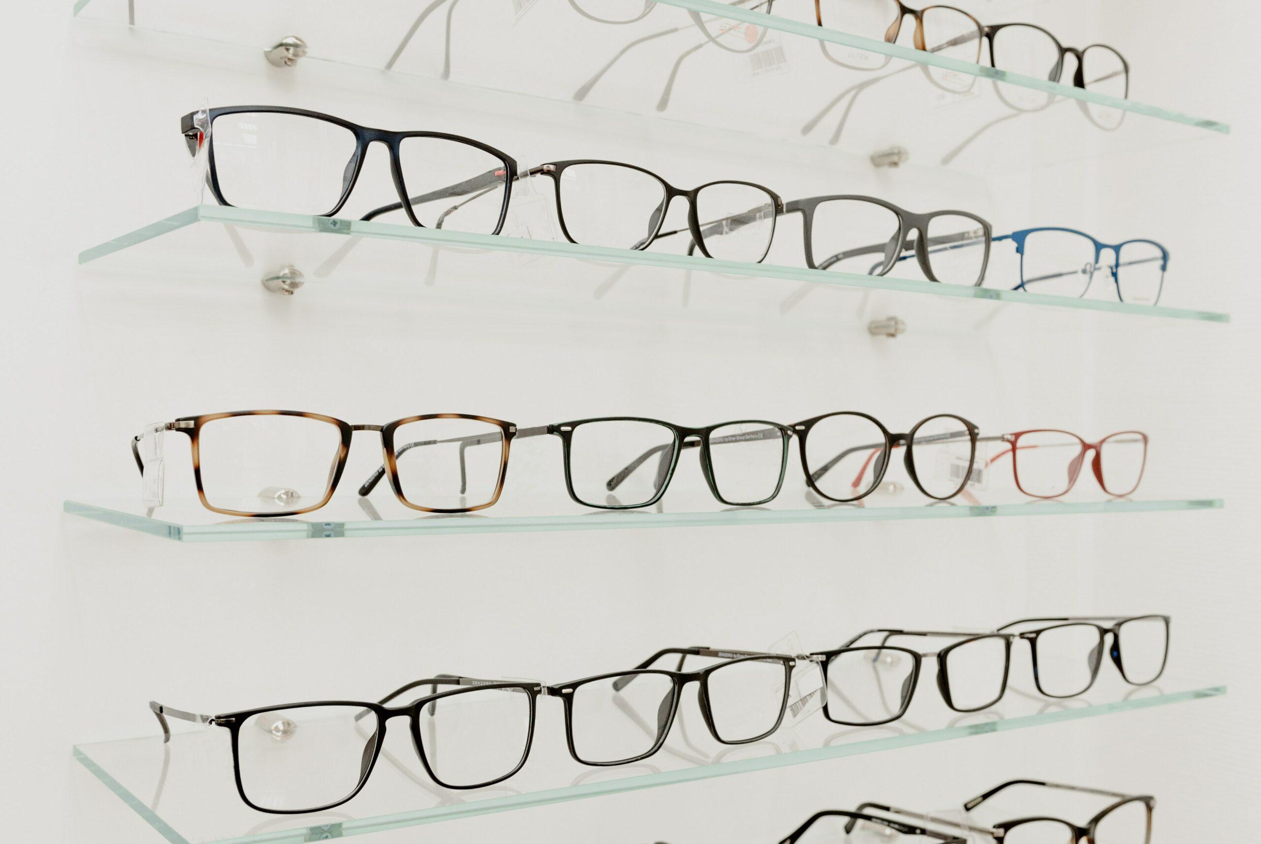 Vemos uma prateleira cheia de óculos de grau (imagem ilustrativa). Texto: franquia ótica diniz.