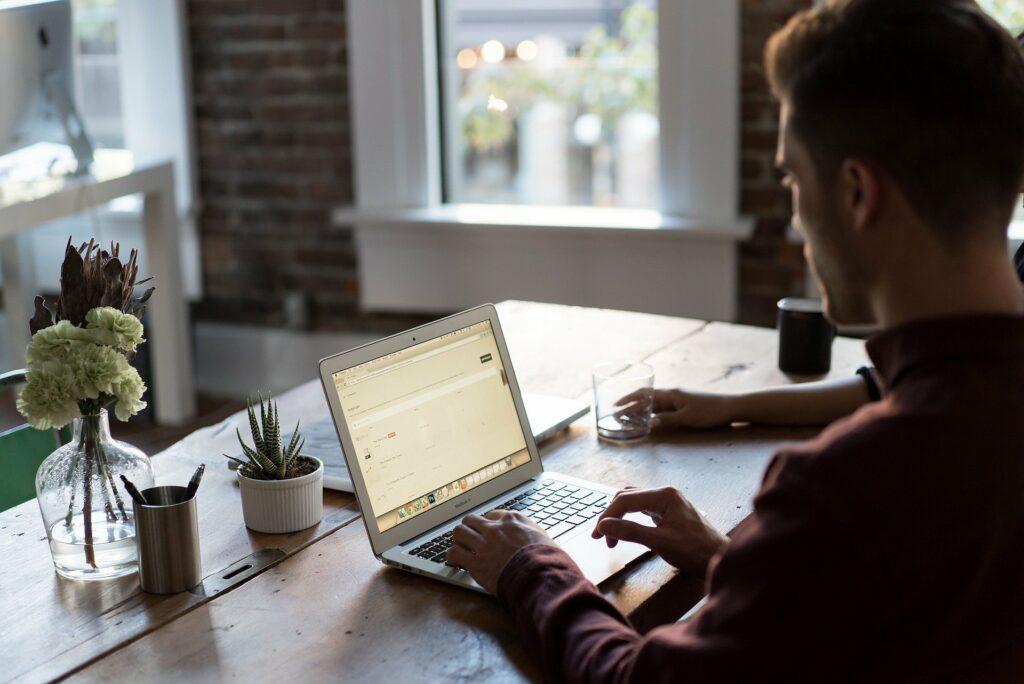 Vemos um homem trabalhando em home office (imagem ilustrativa). Texto: franquia San Martin.