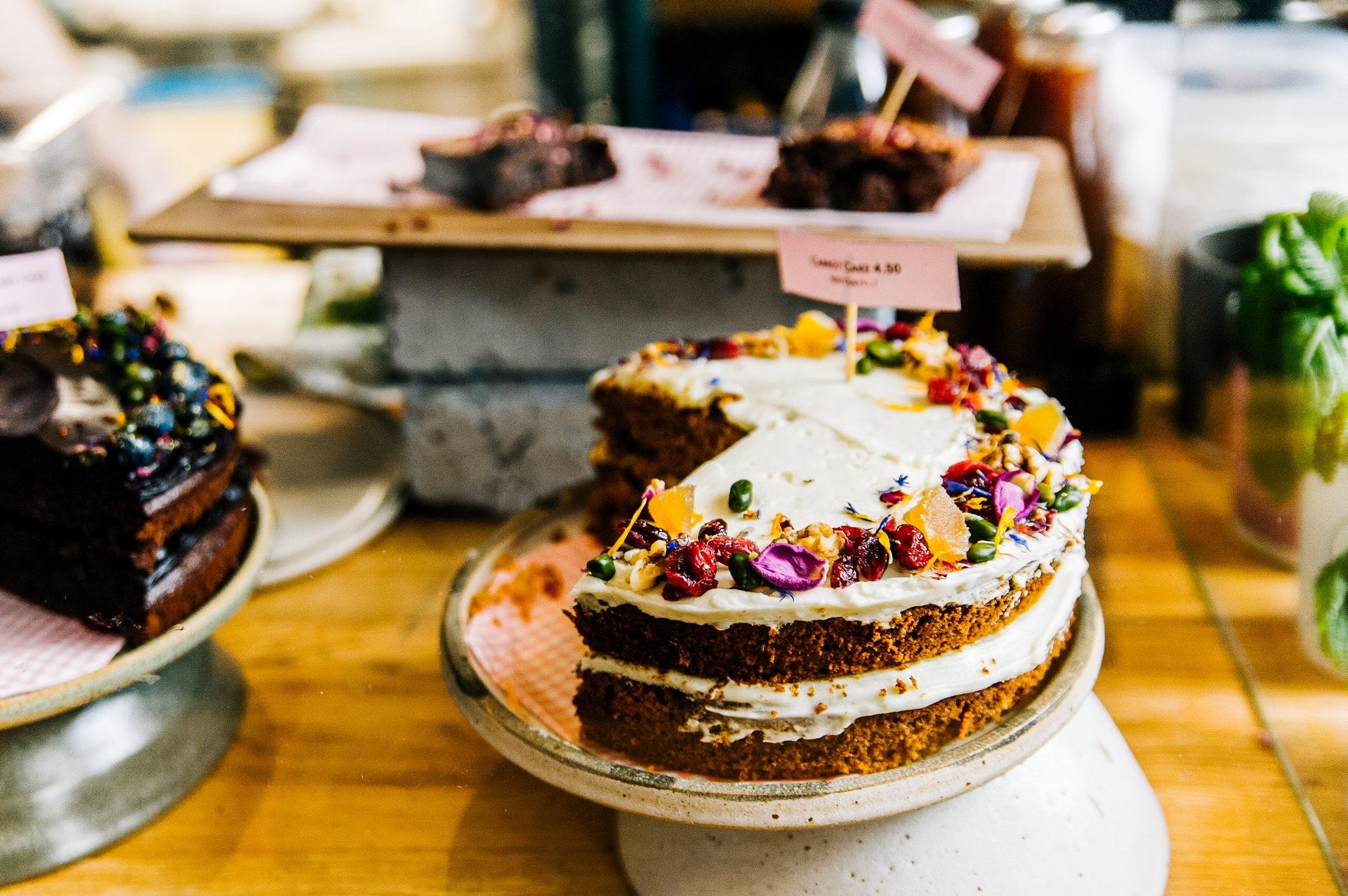 Vemos um bolo com cobertura de frutas silvestres secas e mais alguns, à direita e ao fundo, sobre uma mesa (imagem ilustrativa). Texto: franquia Sodiê Doces.