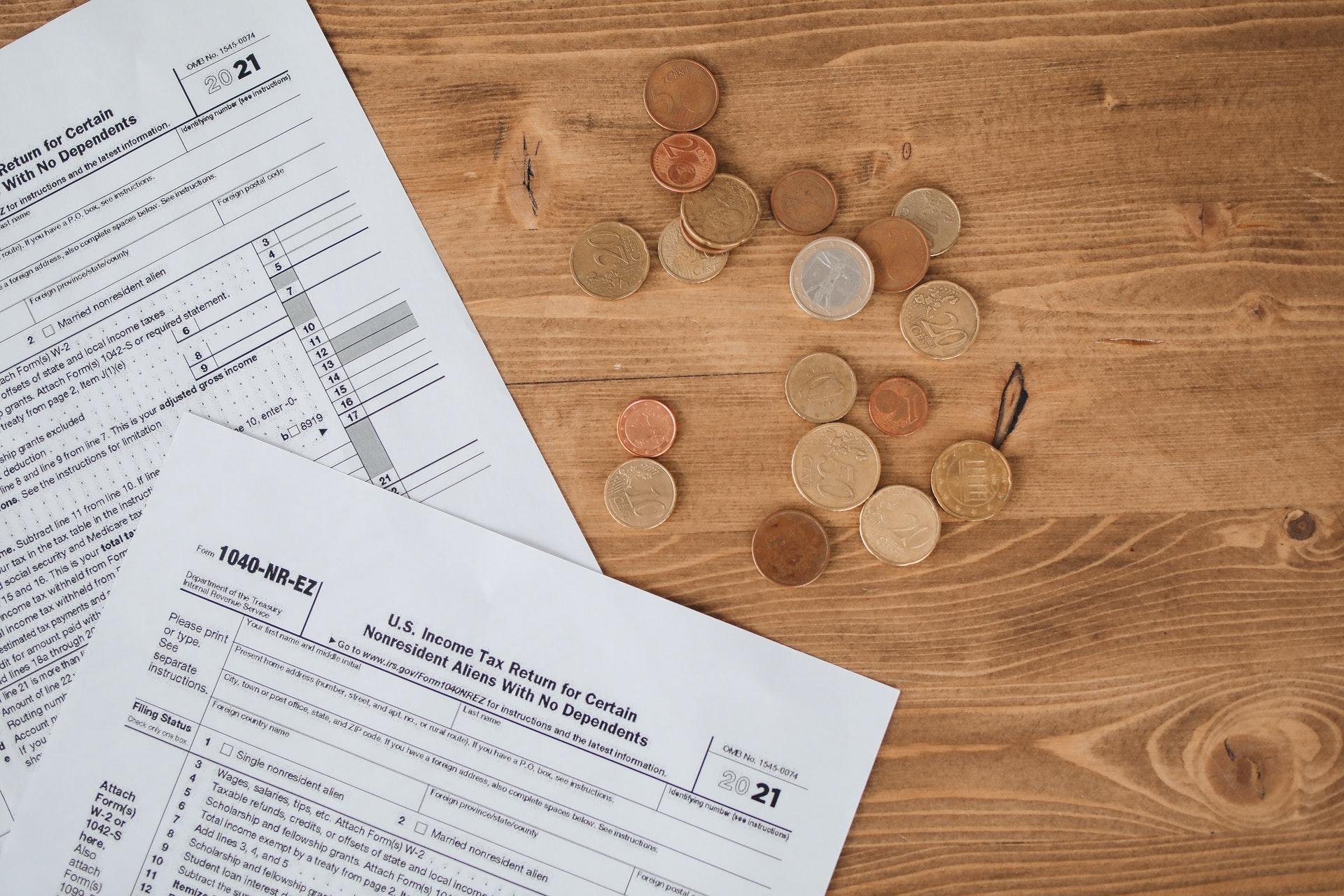 Vemos duas folhas de papel e algumas moedas sobre uma mesa (imagem ilustrativa). Texto: franquia Sodiê Doces.