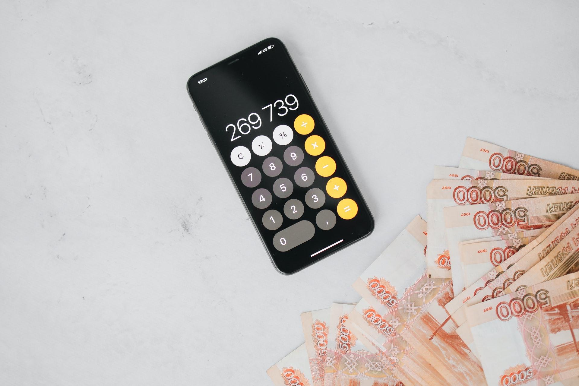 Vemos uma calculadora em um celular e notas de dinheiro sobre uma mesa (imagem ilustrativa). Texto: franquia touareg seguros.
