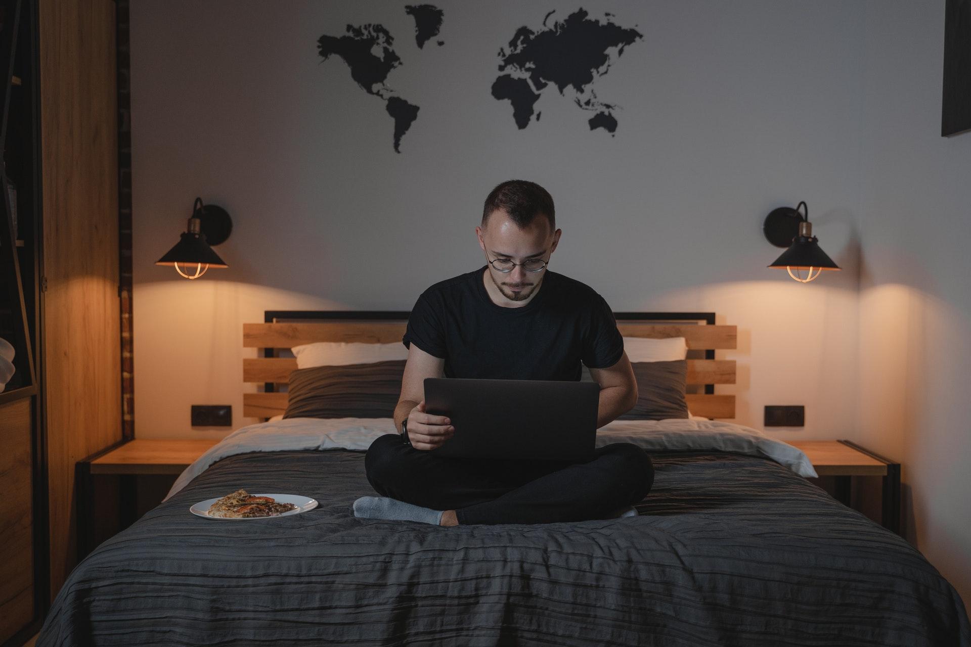Vemos um homem sentado em sua cama enquanto trabalha; à esquerda da imagem é possível ver um prato contendo um lanche (imagem ilustrativa). Texto: franquia TSValle Corretora de Seguros.