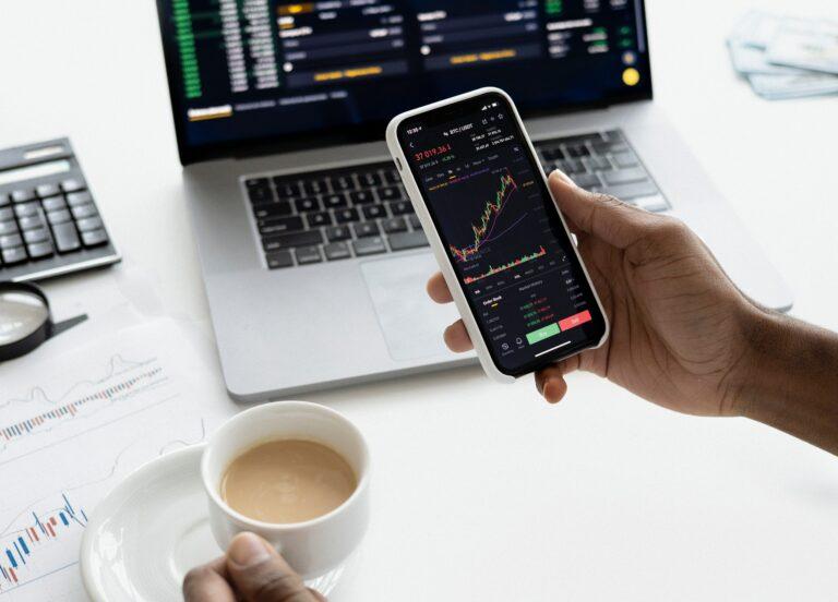 Imagem de um celular e um computador com gráficos diversos. Imagem ilustrativa texto franquai TSValle Corretora de Seguros.