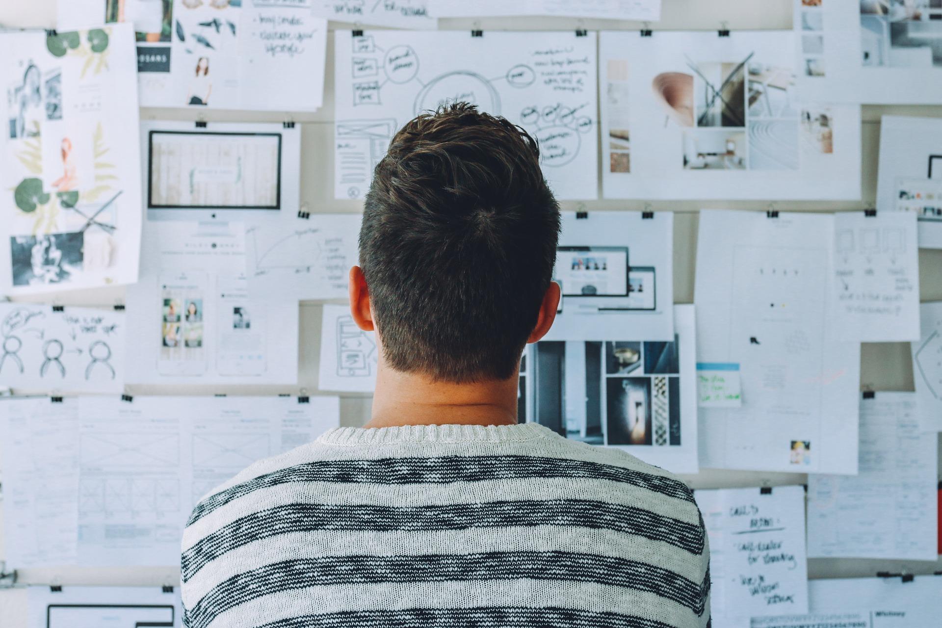Vemos um homem olhando para uma parede cheia de informações (imagem ilustrativa). Texto: franquias de turismo.
