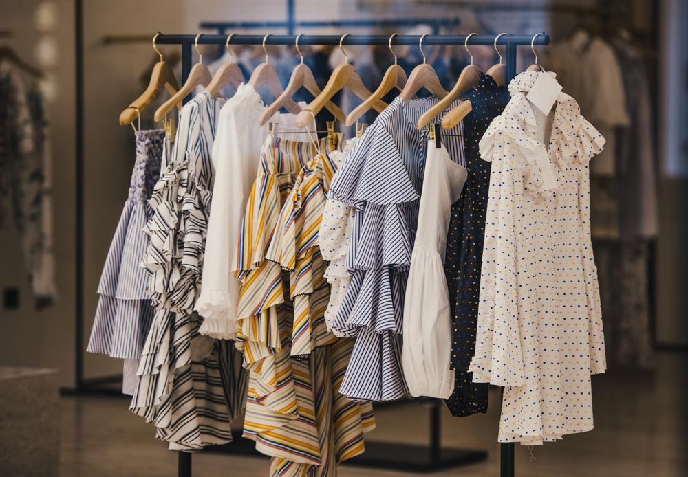 Vemos algumas peças de roupas em uma arara de loja (imagem ilustrativa). Texto: franquias nacionais.