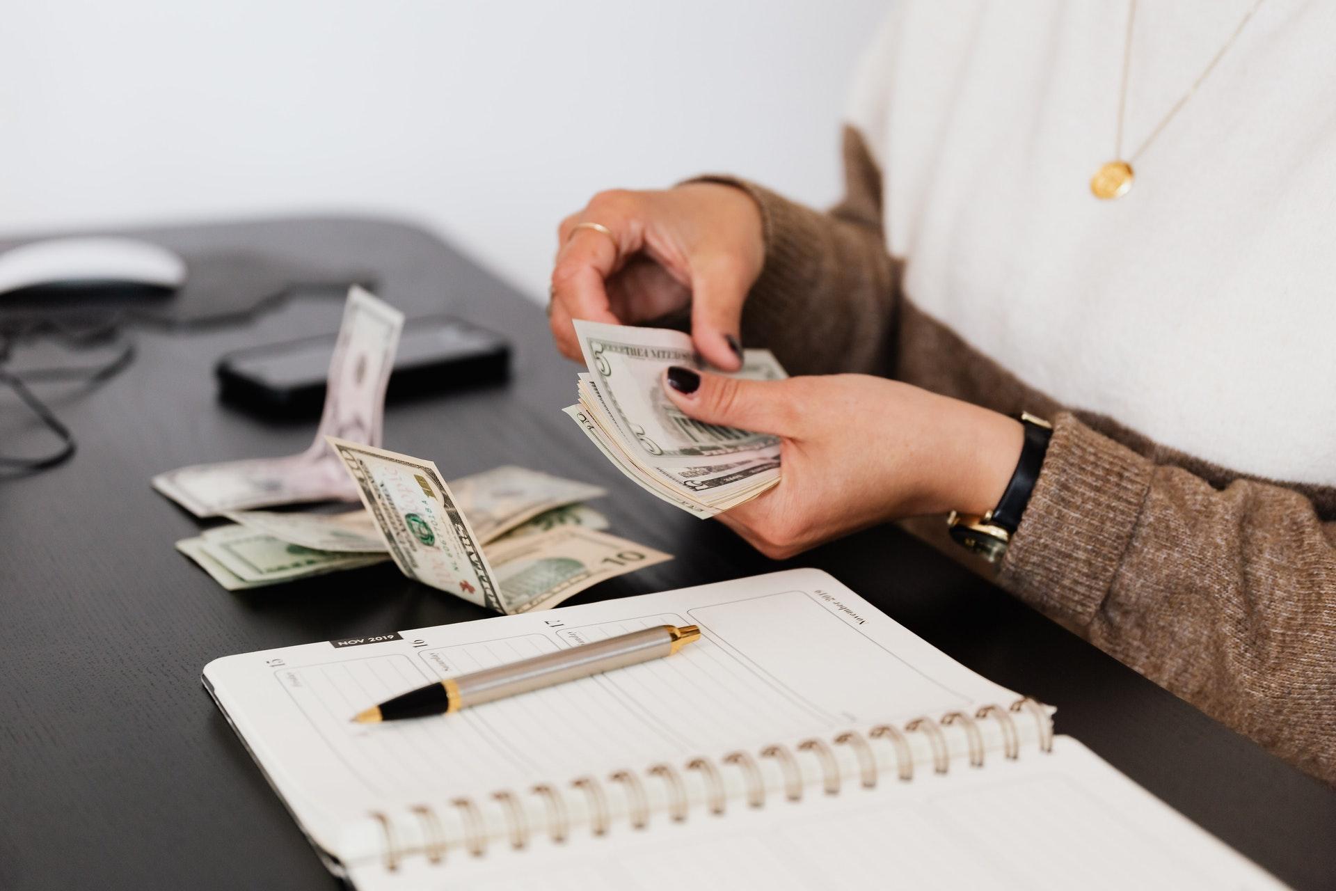 Vemos uma pessoa contando dinheiro sentada à mesa com uma agenda por perto (imagem ilustrativa). Texto: investir meu dinheiro de forma segura.