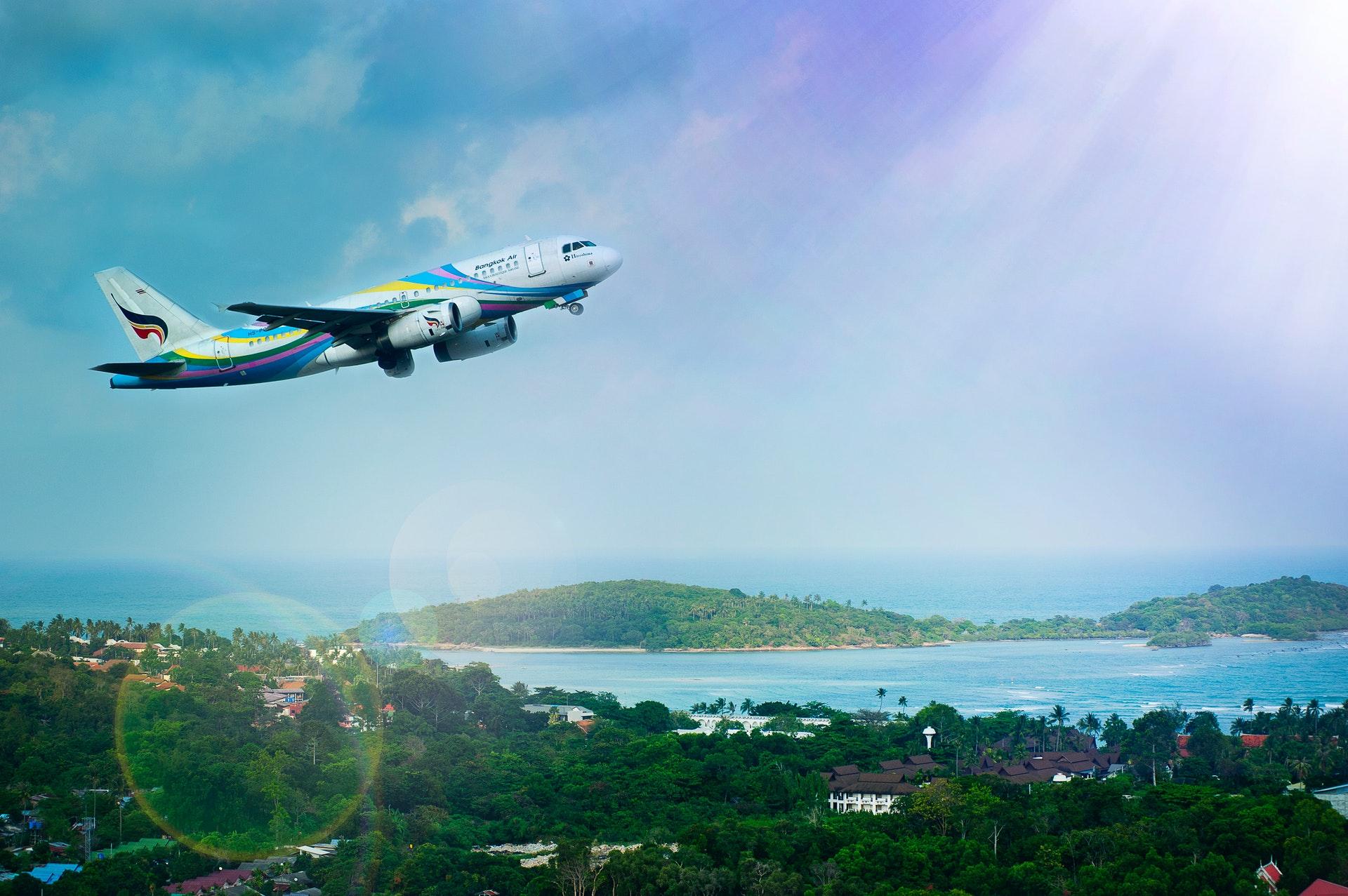 Vemos um avião no céu e uma praia ao fundo (imagem ilustrativa). Texto: investir meu dinheiro de forma segura.