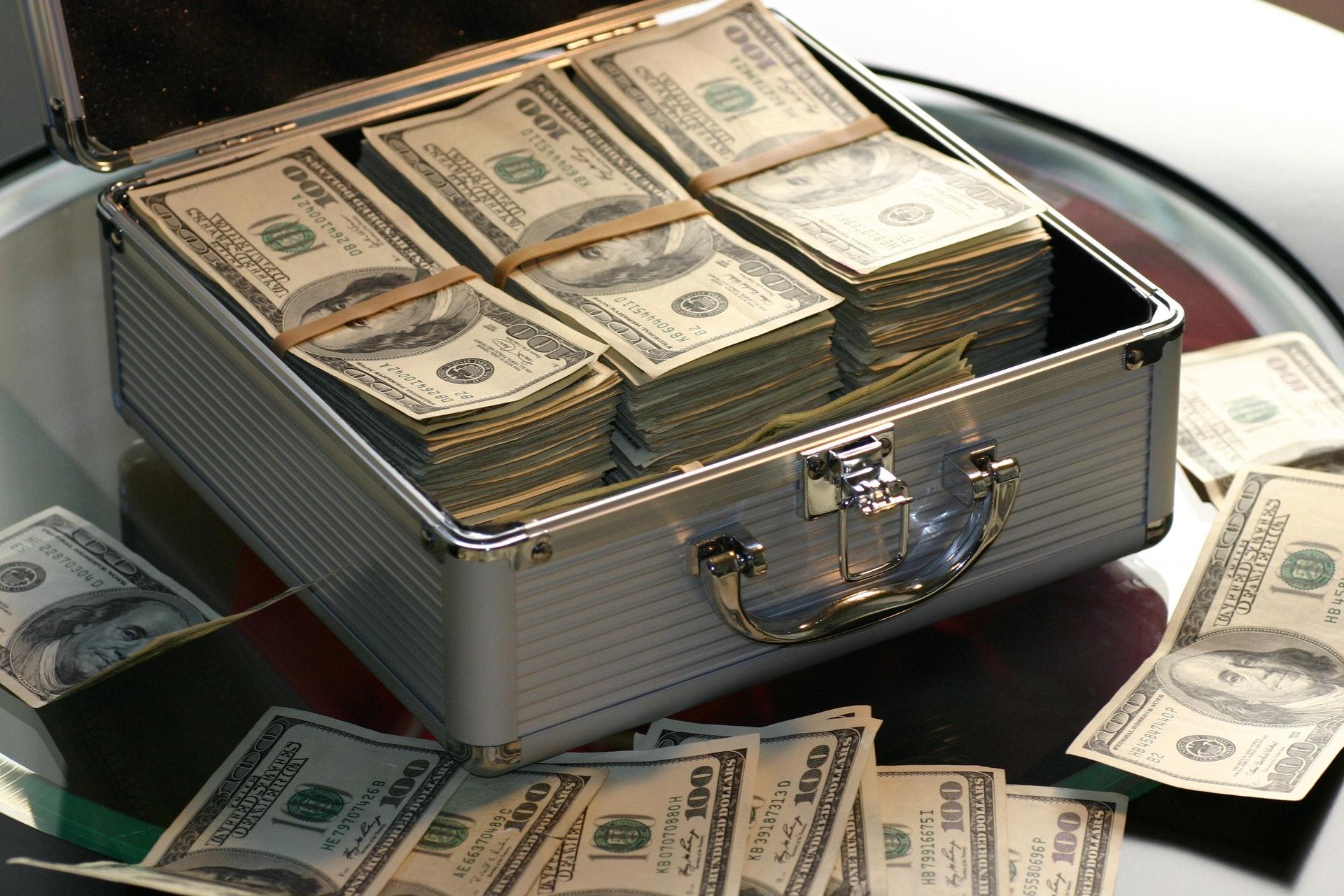Imagem de uma maleta cheia de dólares e notas de dólar ao redor. Imagem ilustrativa texto investir meu dinheiro de forma segura.