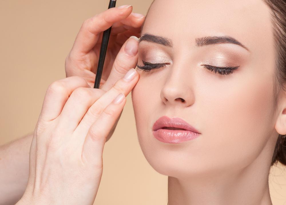 Vemos que uma profissional está aplicando cílios postiços de uma mulher (imagem ilustrativa). Texto: franquia de estética.