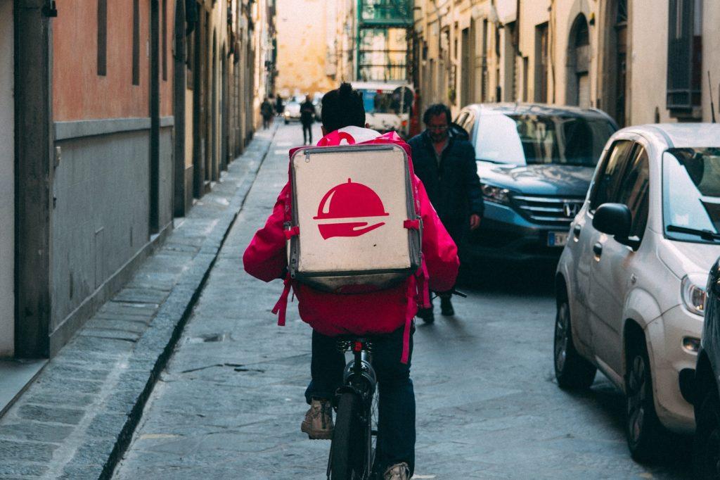 Vemos um entregador a caminho de uma residência (imagem ilustrativa). Texto: mercado de food service.