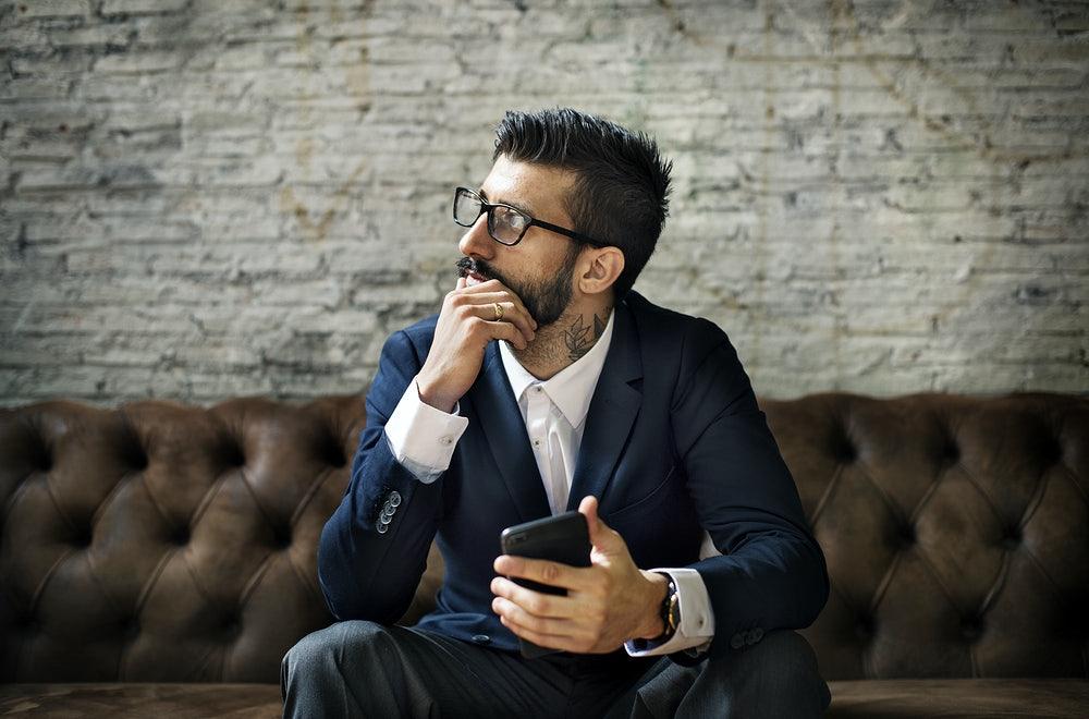 Vemos um homem com semblante pensativo, sentado em um sofá, com o celular à mão (imagem ilustrativa).