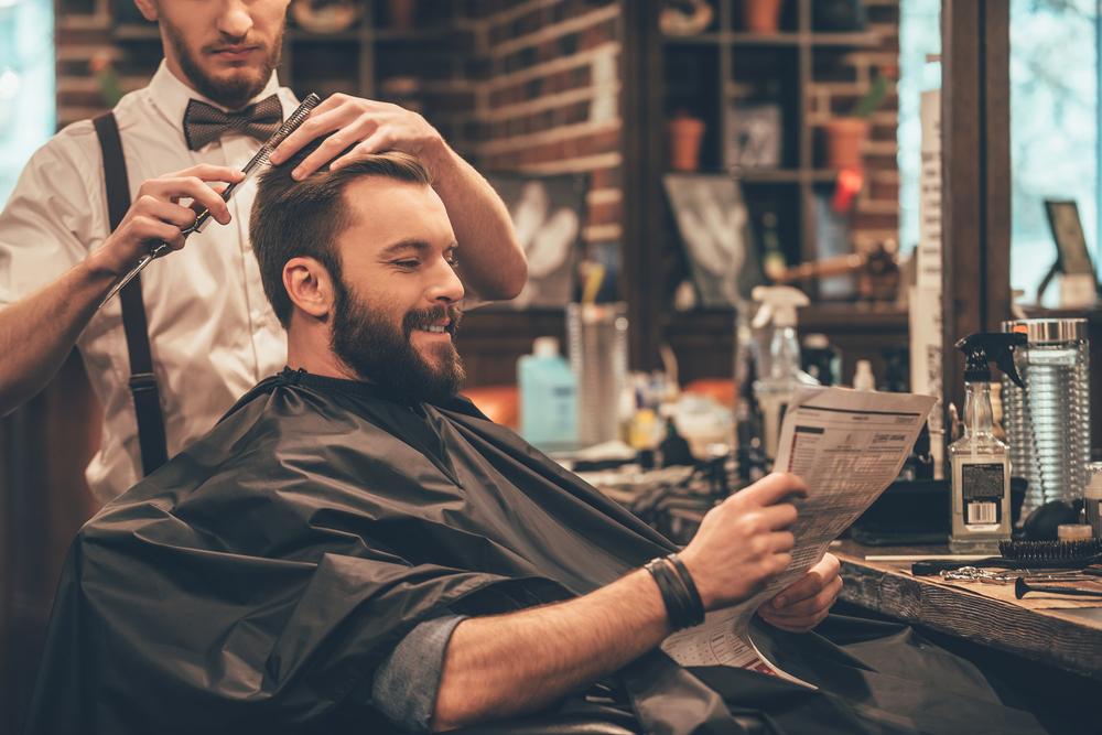 Vemos um homem ser atendido em uma barbearia enquanto lê um jornal (imagem ilustrativa). Texto: modelos de franquias de beleza.