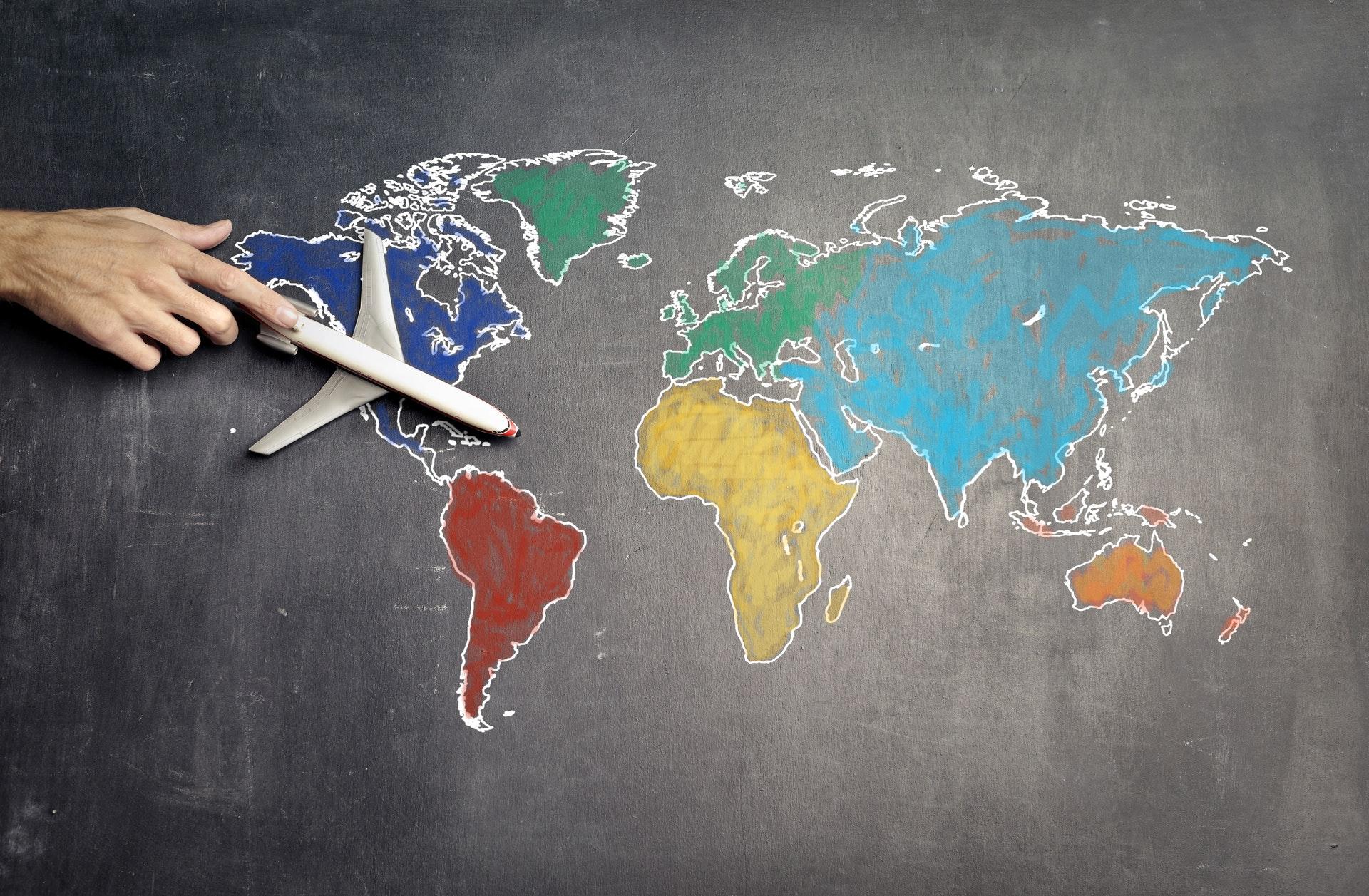 Vemos, desenhado em um quadro-negro, todos os continentes do mundo; uma pessoa, que tem uma miniatura de avião nas mãos, guia o objeto por entre as linhas do desenho (imagem ilustrativa). Texto: negócios em alta 2021.