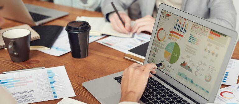 Imagem de uma pessoa vendo gráficos em um computador. Imagem ilustrativa texto negócios em alta 2021.