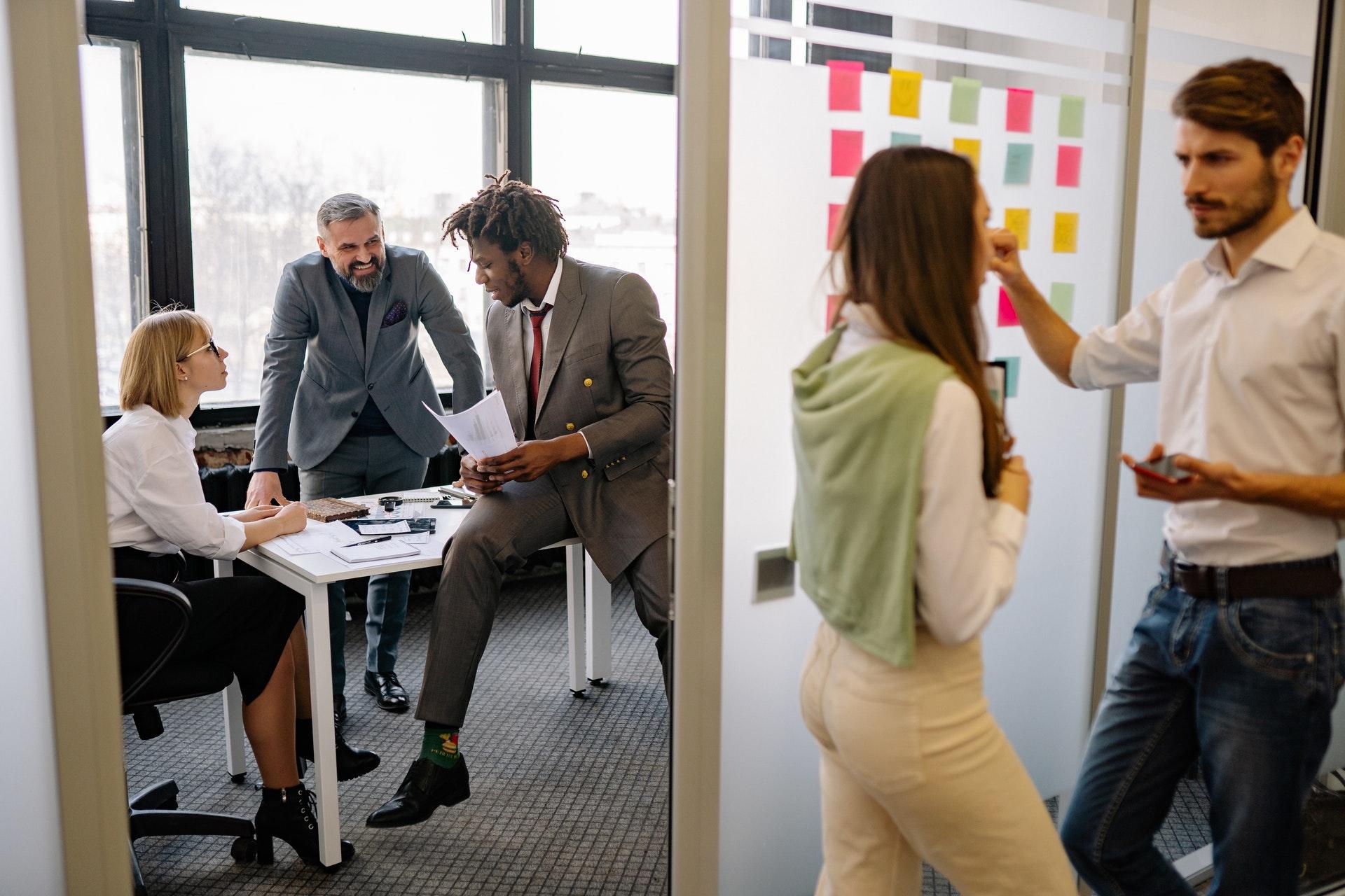 Imagem de pessoas em um escritório conversando. Imagem ilsutra