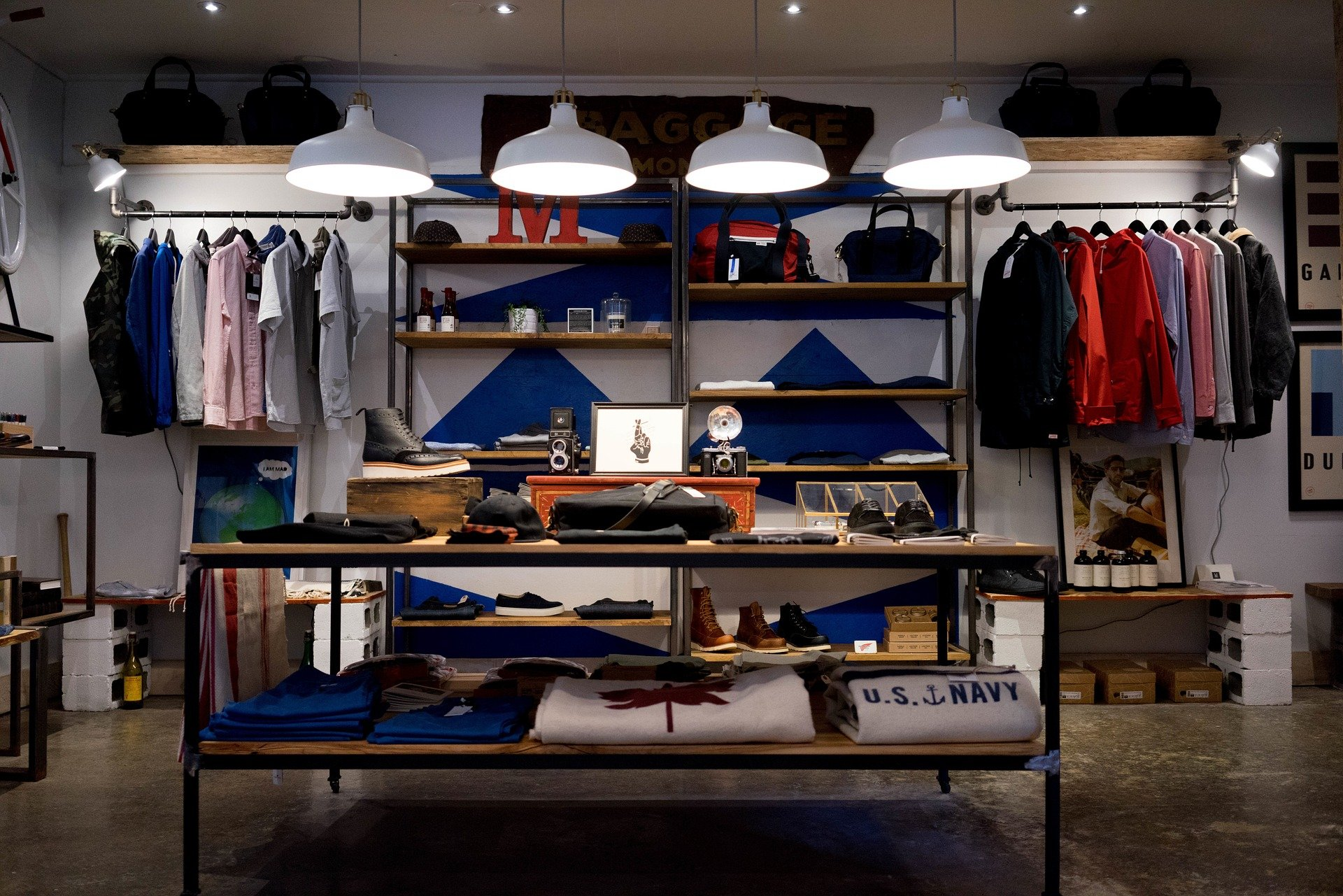 Vemos uma loja de roupas com prateleiras e peças em cabides (imagem ilustrativa).