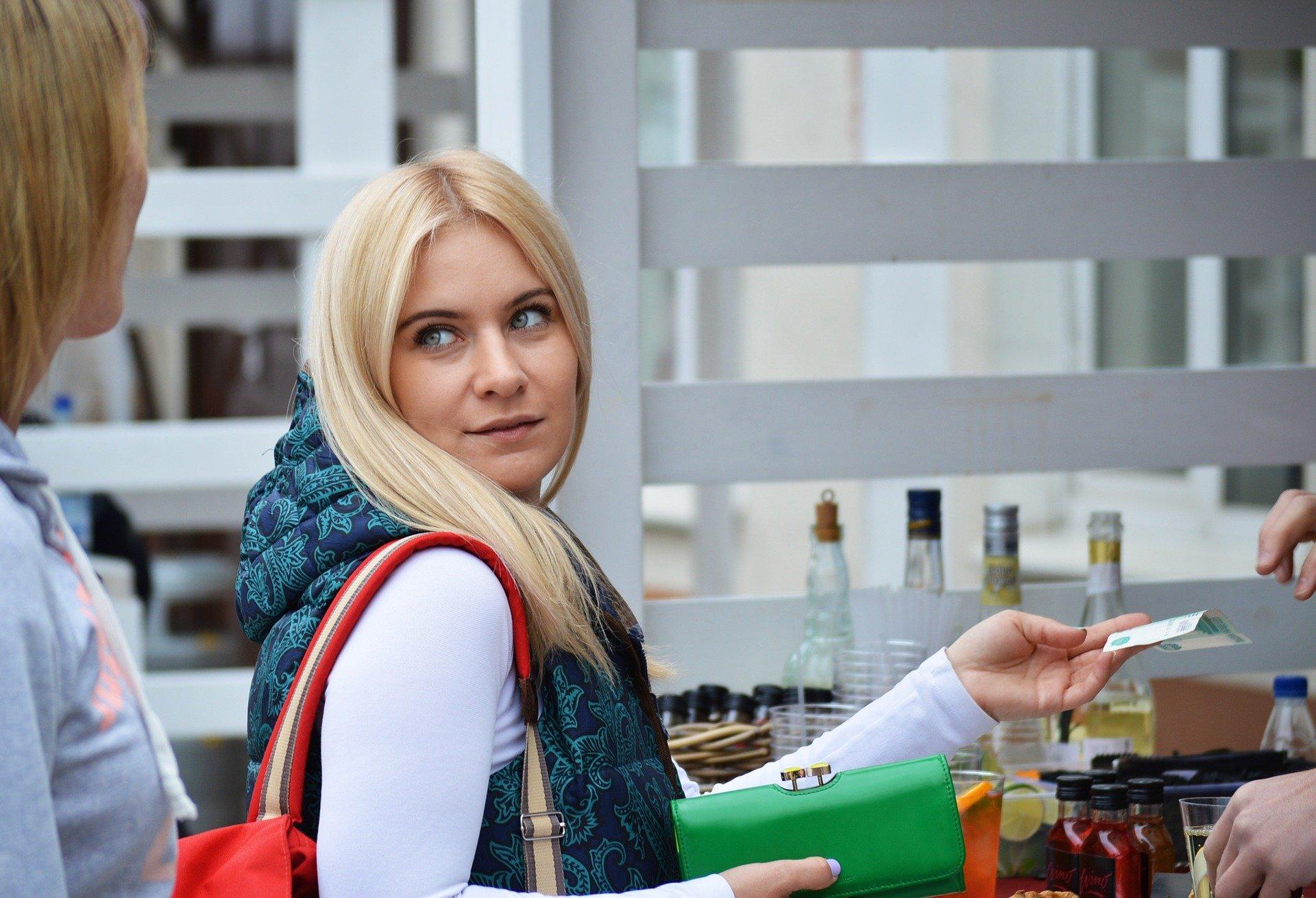 Vemos uma mulher loira pagando um produto em uma loja (imagem ilustrativa). Texto: qual o melhor tipo de negócio para abrir.