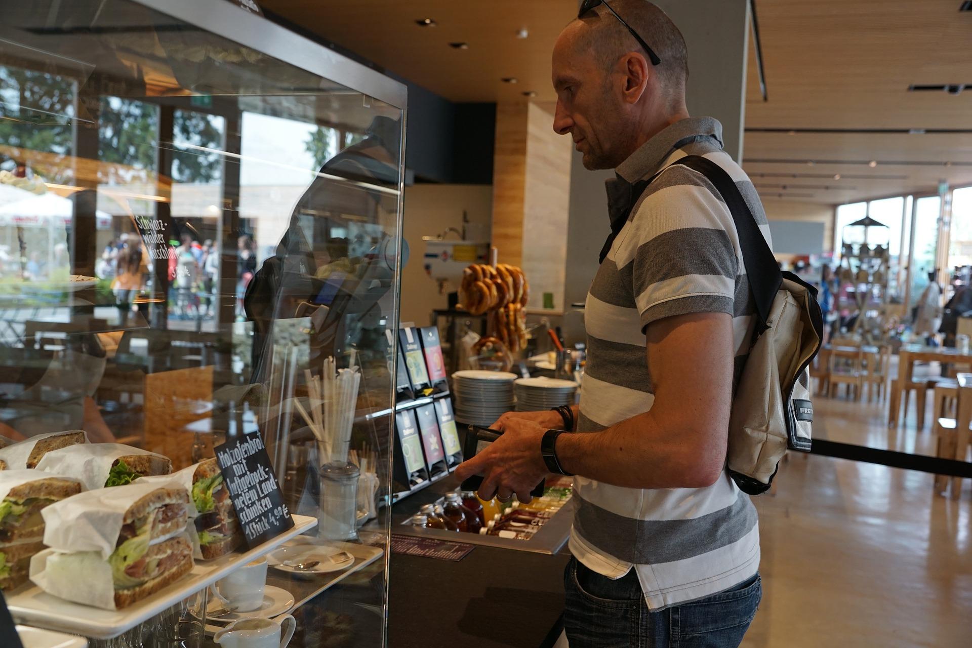 Vemos um homem em frente a um balcão de padaria enquanto olha para os produtos ali expostos (imagem ilustrativa).
