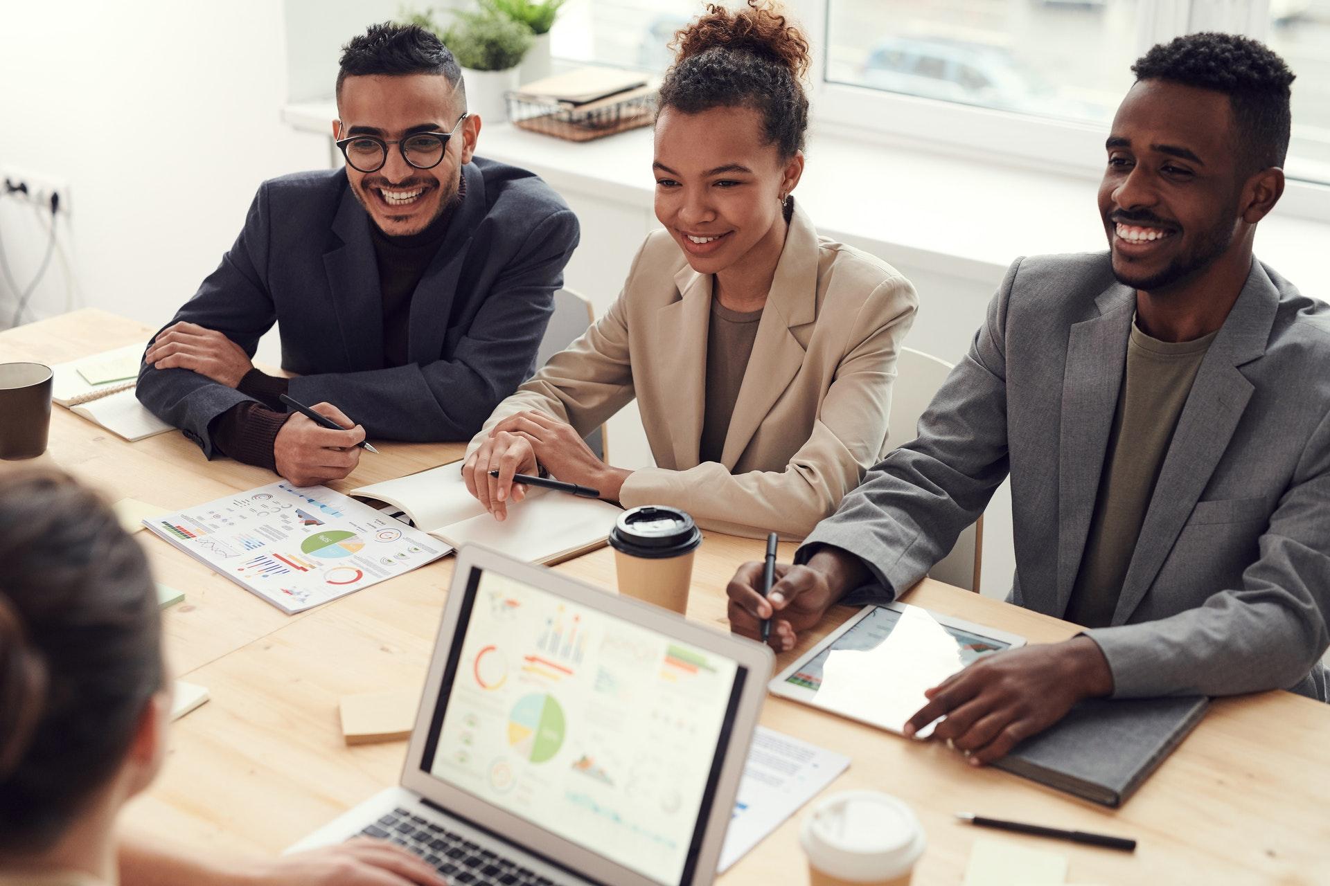 Vemos três empresários (dois homens e duas mulheres) reunidos em uma mesa de escritório para uma reunião (imagem ilustrativa). Texto: ramo para empreender.