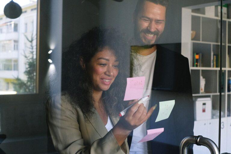 Imagem de uma mulher colando um papel em um vidro. Imagem ilustrativa texto ramo para empreender.